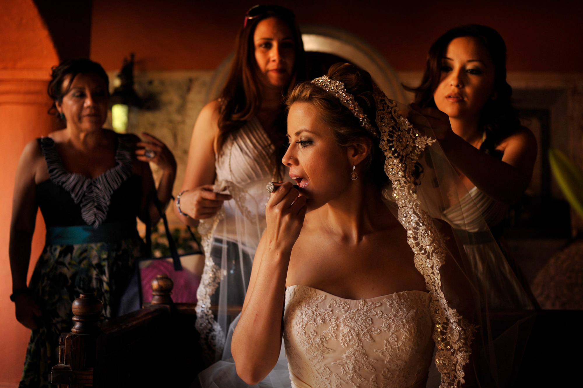 Bride puts on her lipstick while bridesmaid adjust veil - Daniel Aguilar Photographer