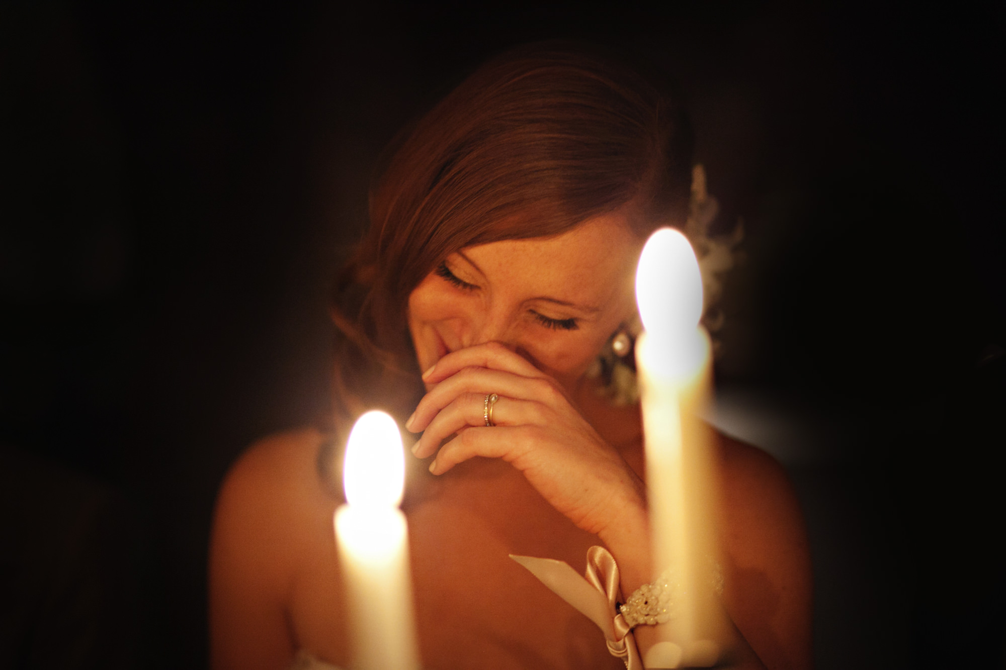 Bride shyly laughs behind candleight- PhotoJJ