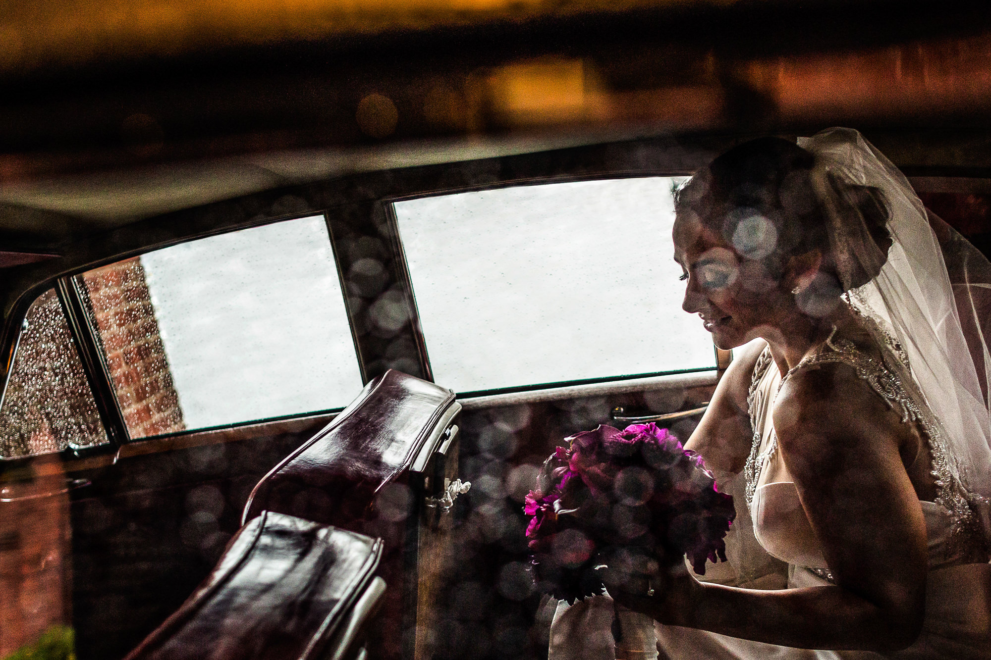 Bride in limo with fuschia bouquet - photo by JAG Studios