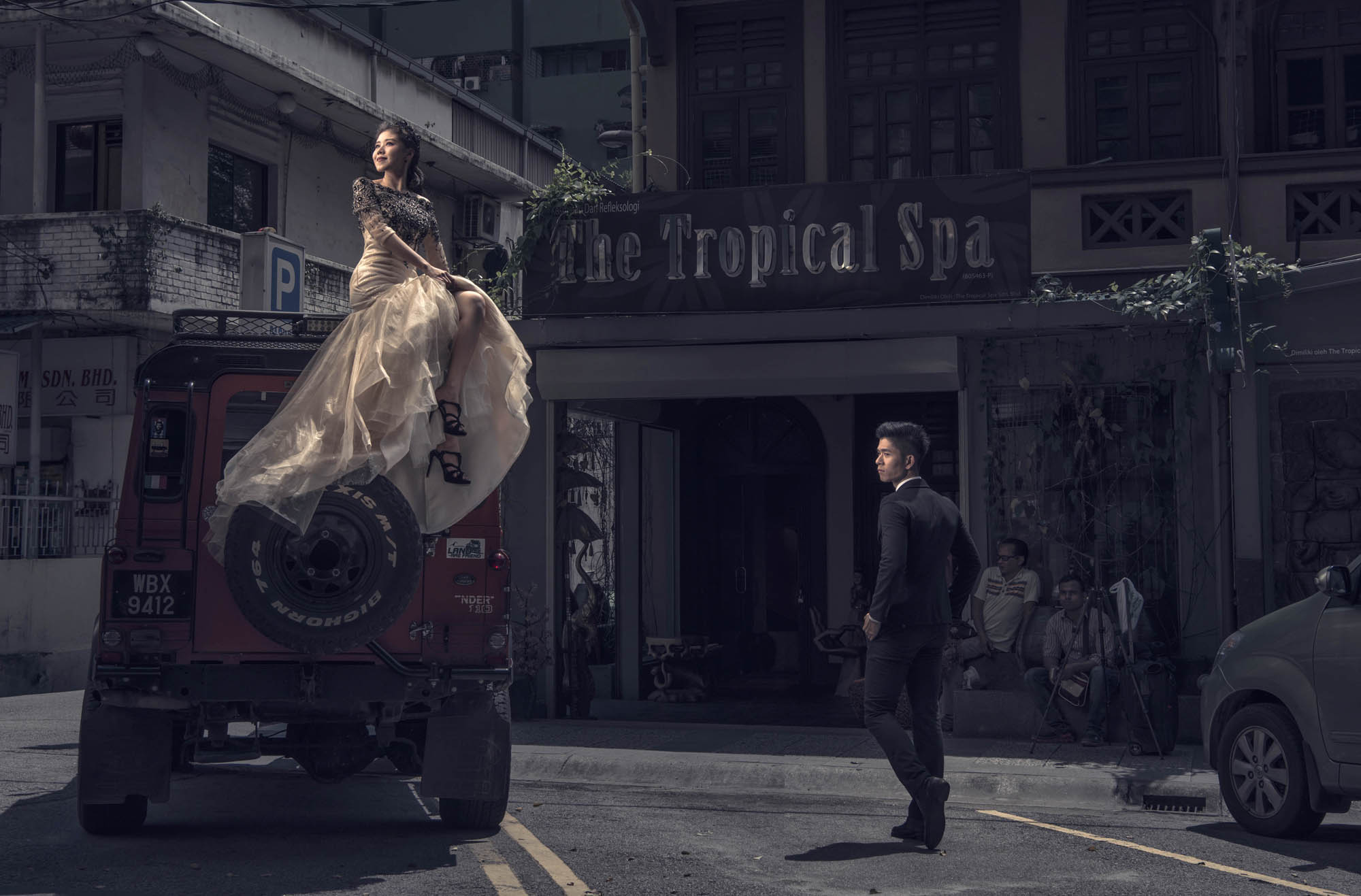 Bride sitting on jeep with groom walking by, by CM Leung