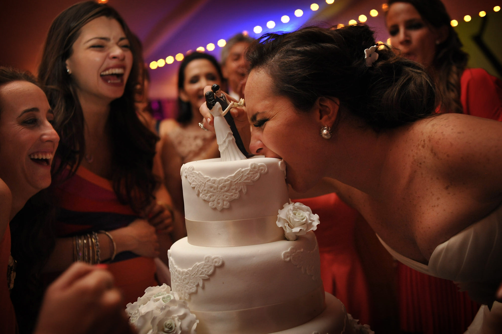 Bride bites into whole wedding cake - Daniel Aguilar Photographer