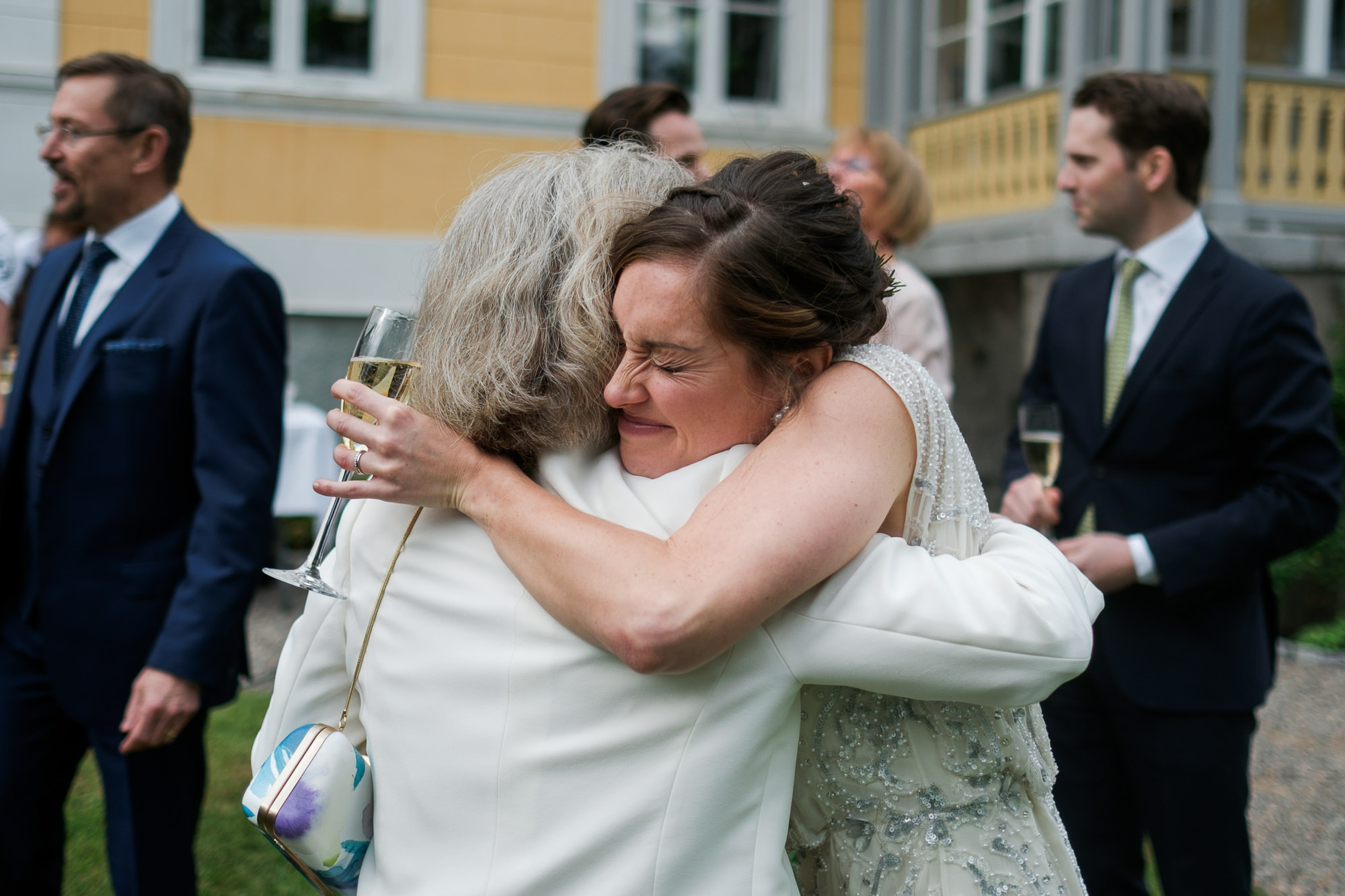 Bride tightly hugs guests photo by Nordica Photography
