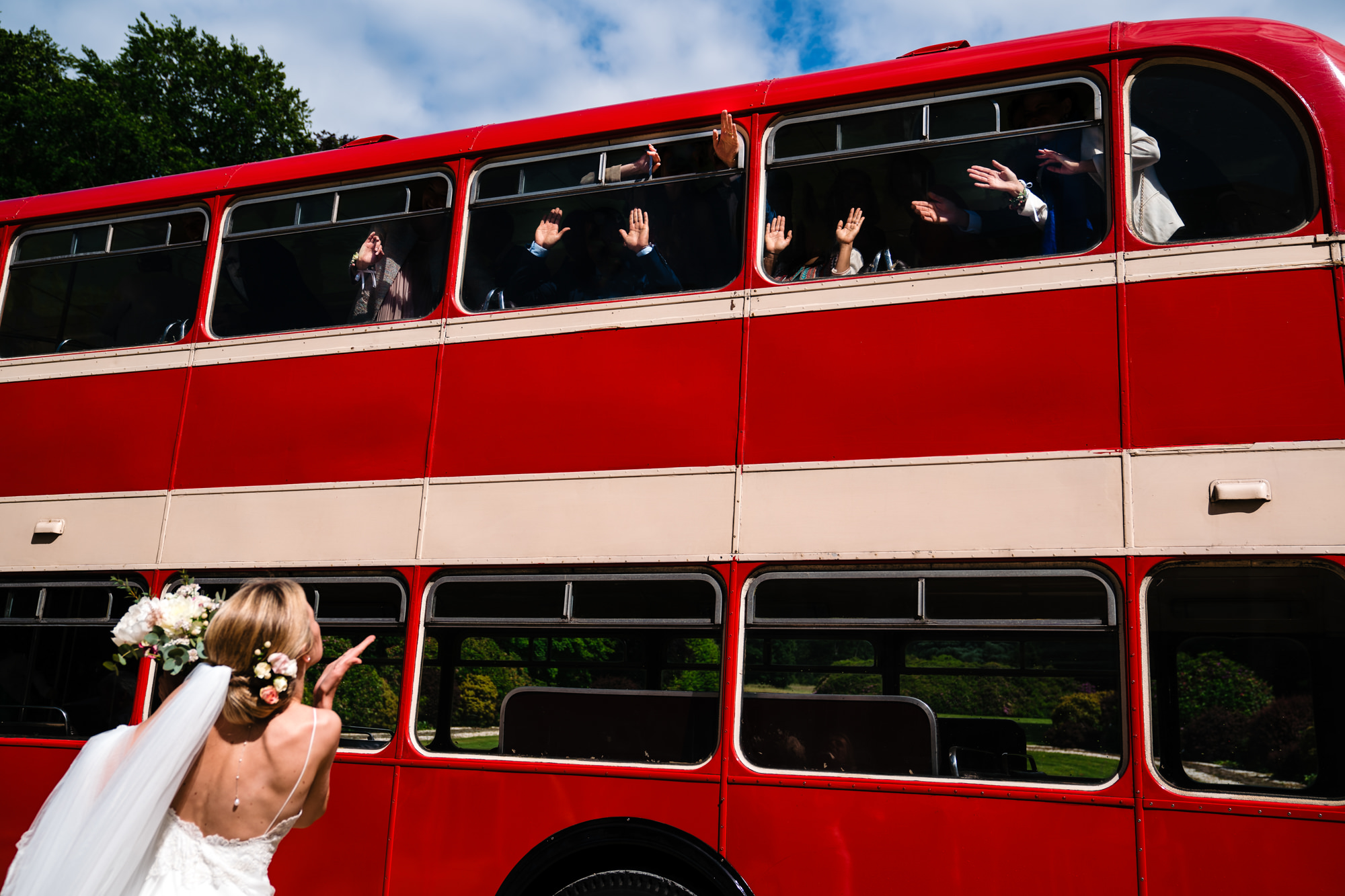 Bride waves goodbye to guest in double decker bus Yves Schepers