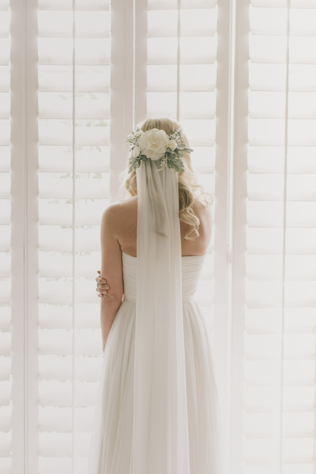 Bride with large white rose floral crown on veil - photo by James Moes