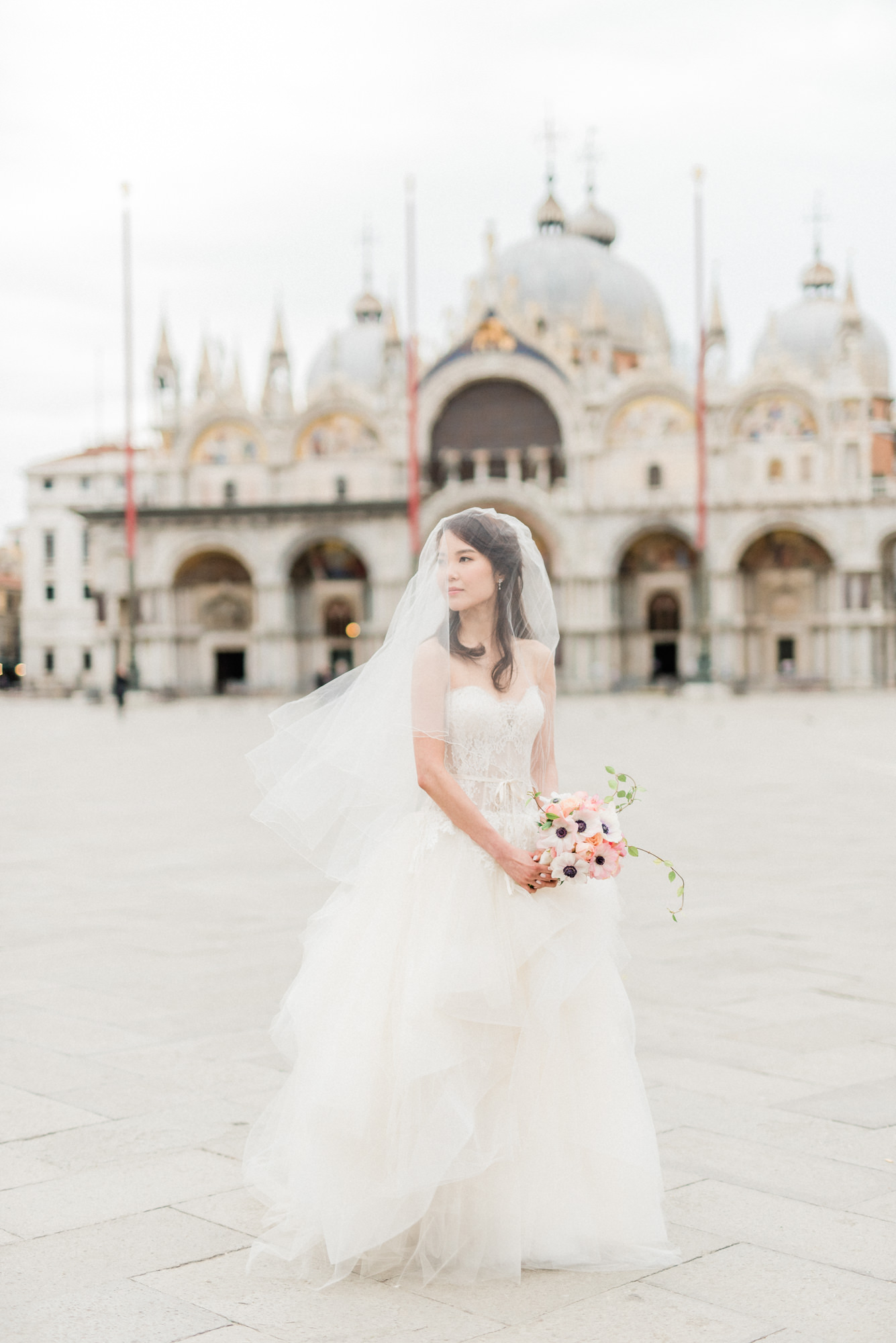 Bride in veil shot wearing a strapless lace gown, by Gianluca Adovasio