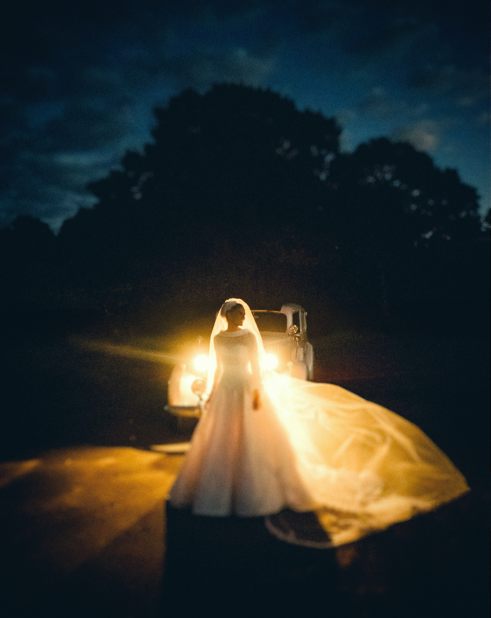 Bride with classic A-line gown lit by headlights photo by Nordica Photography