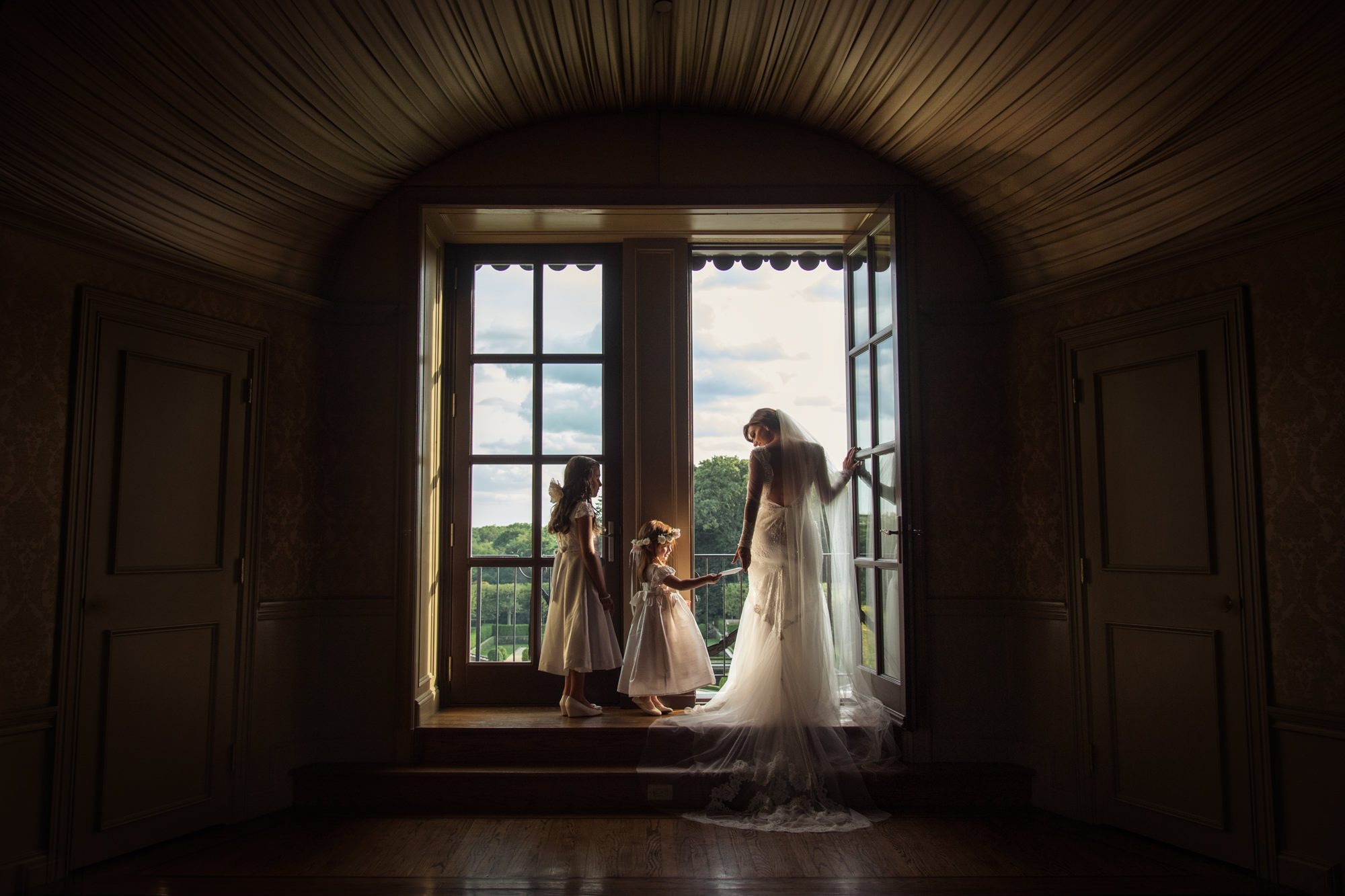 Flower girl checking bride out by window, by Cliff Mautner