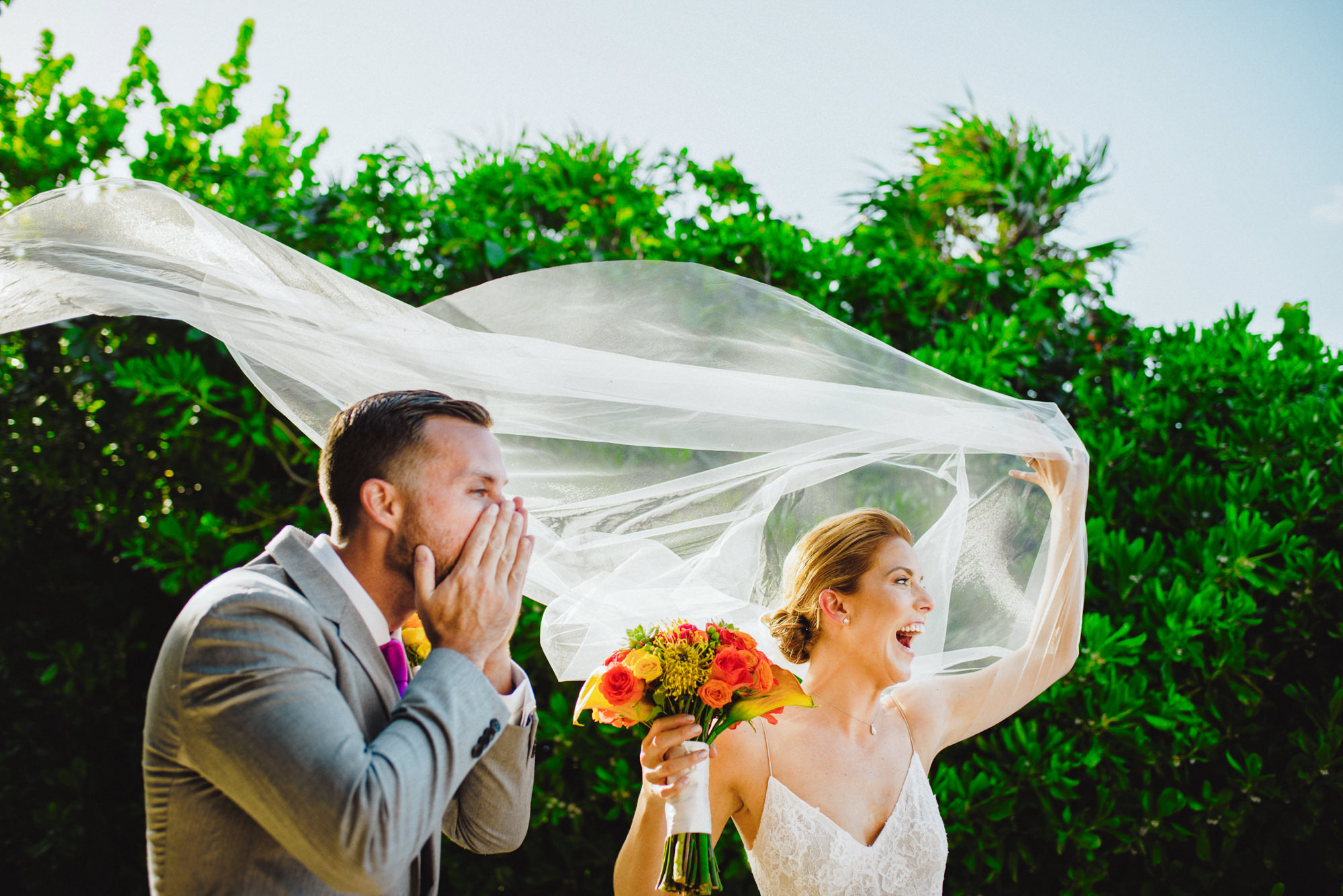 Bride with veil flying in the wind and groom cheering by Fer Juaristi