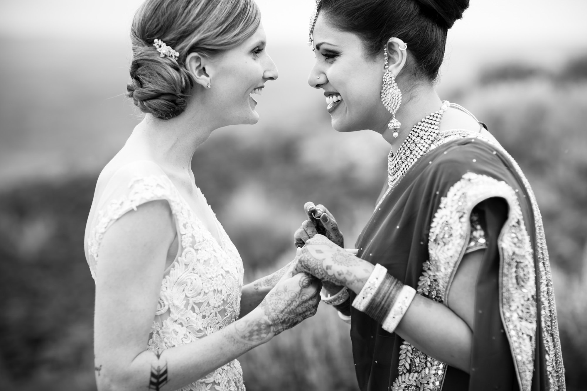 Brides with Indian sari and lace gowns holding hands - La Vie Photography