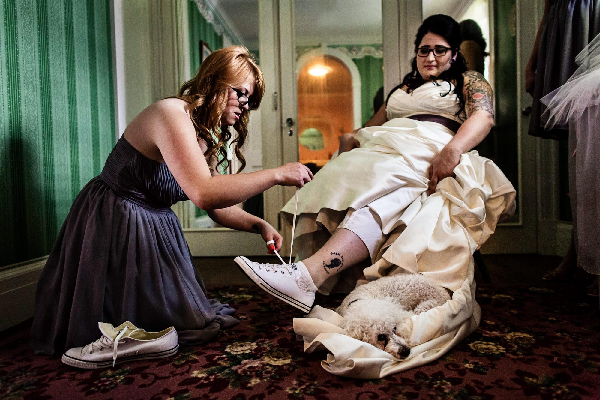 Bridesmaid tieing  sneakers on bride - photo by JAG Studios