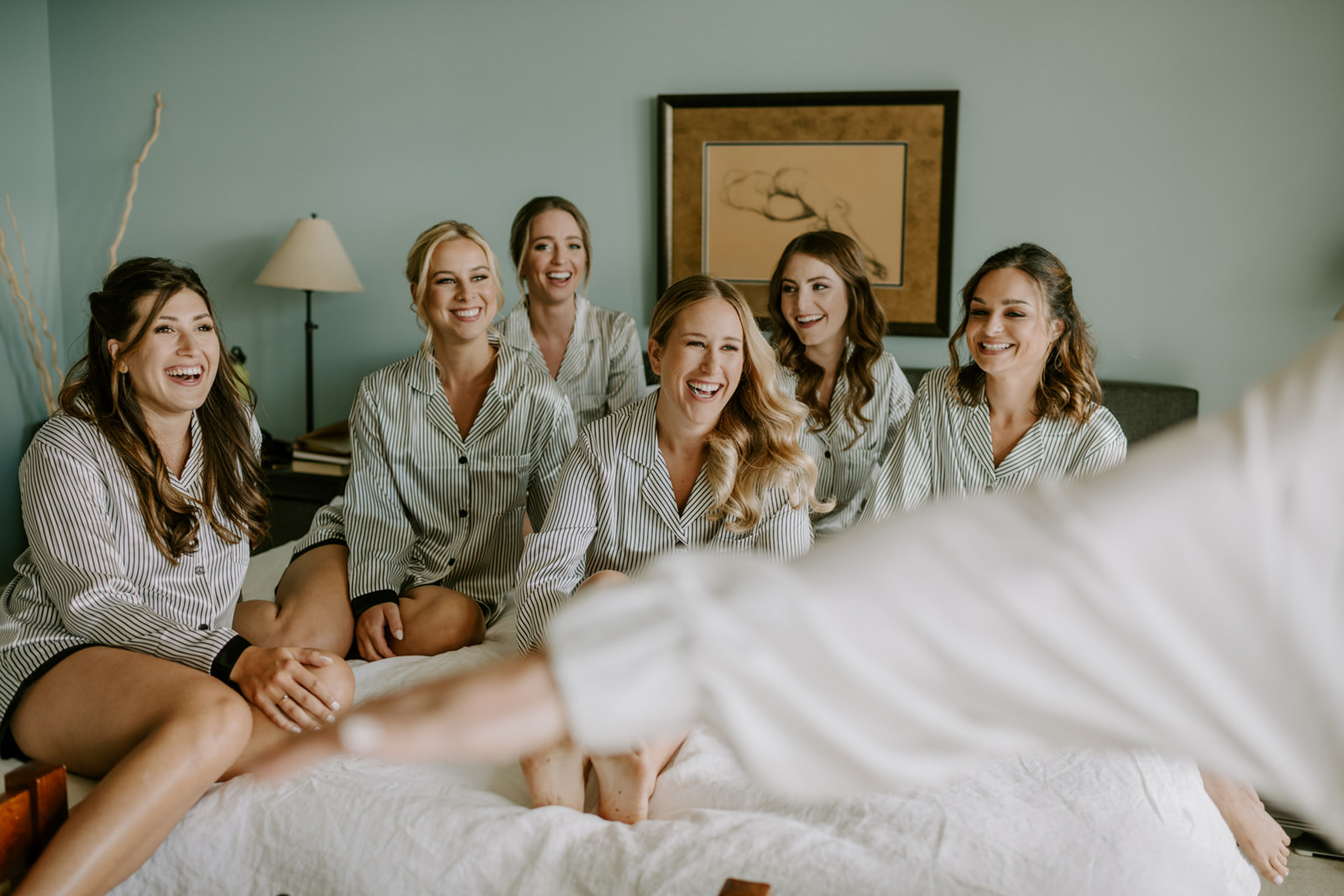 Bridesmaids laughing in matching pajamas- photo by Kristen Marie Parker