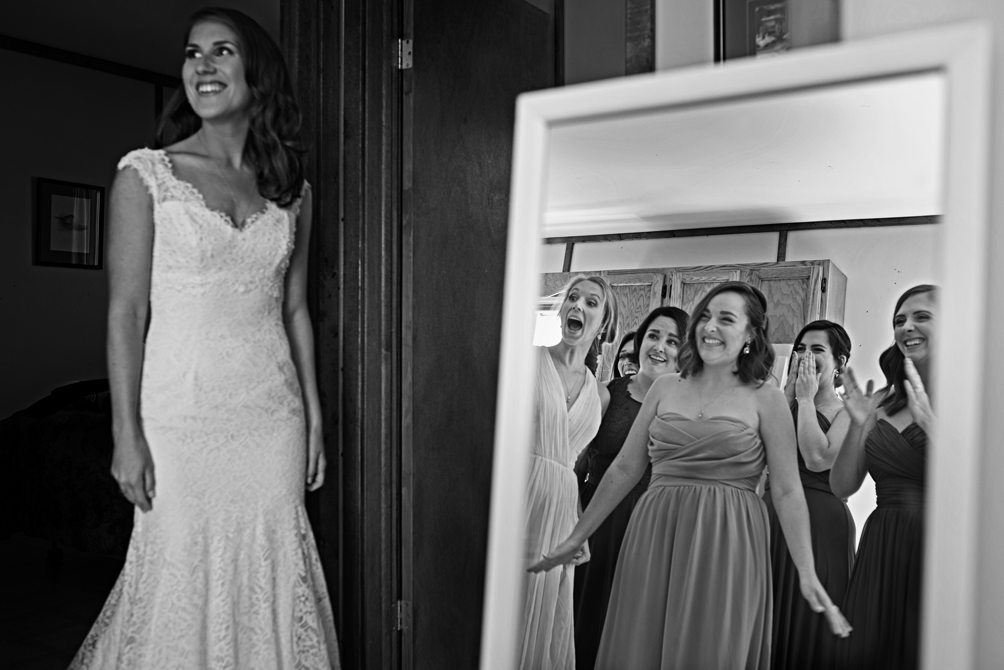 Bridesmaids delighted with bride in dress - photo by Cooked Photography