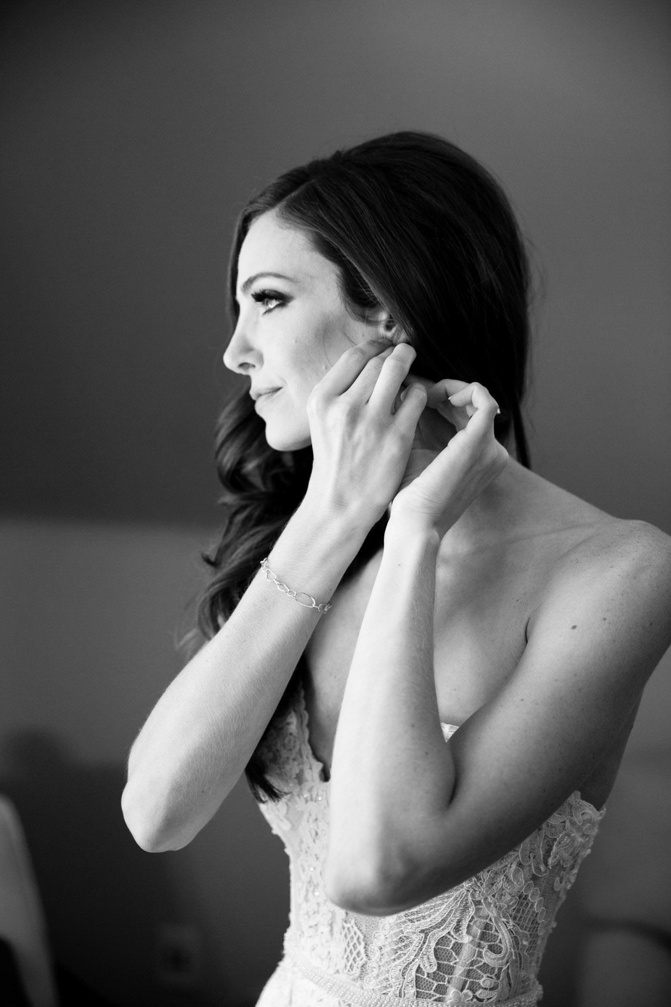 Bride puts on her earring in windowlight - La Vie Photography