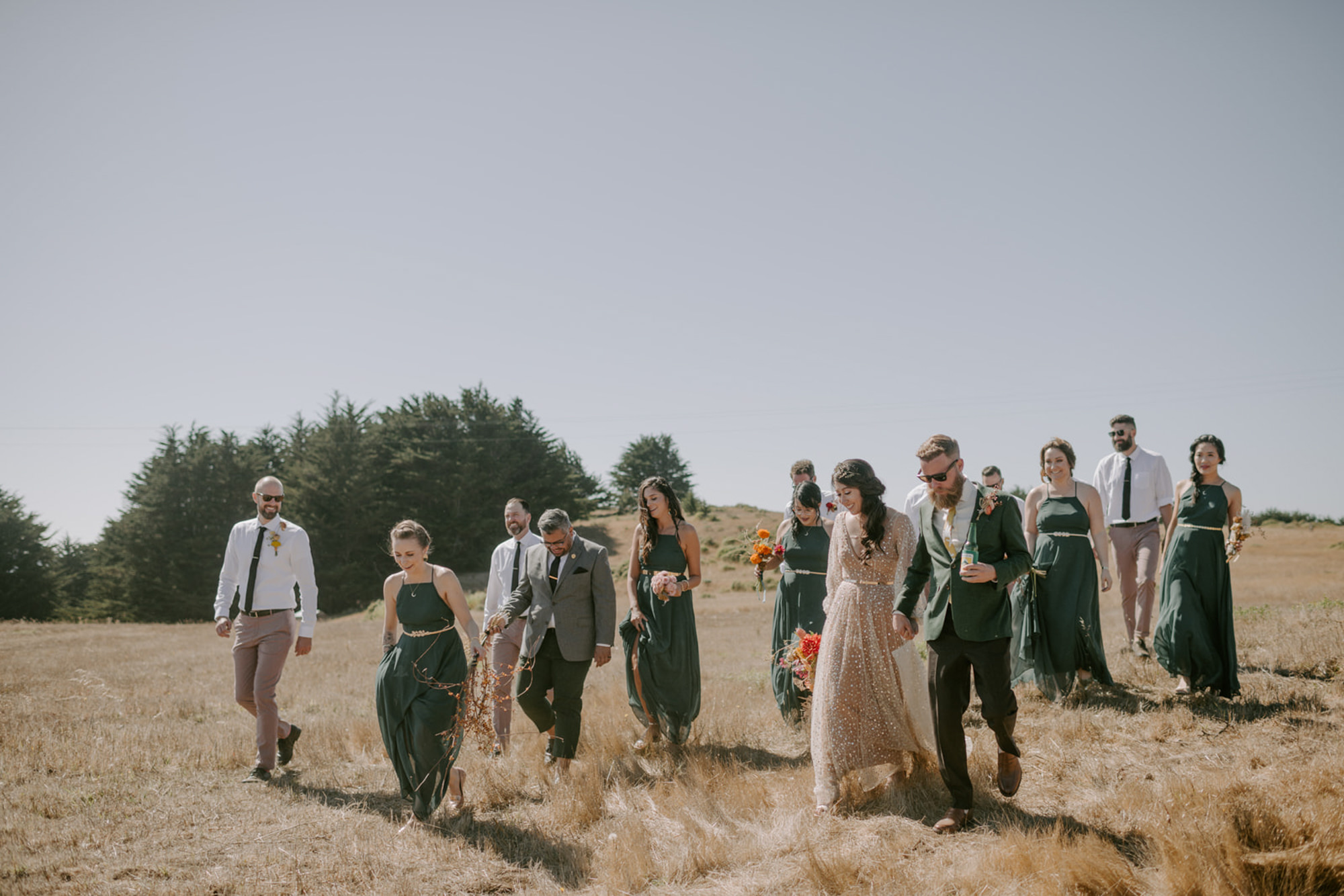 Candid bridal party in grassy field wearing forest green dresses - photo by Kristen Marie Parker