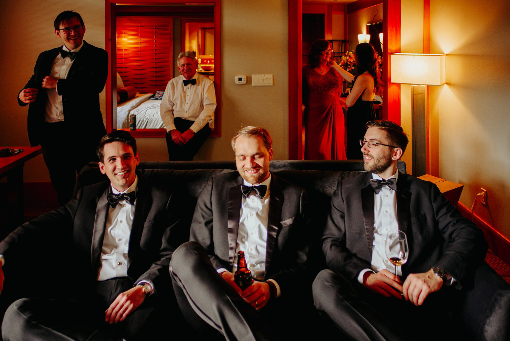 Layered moment of groom, groomsmen and family hanging out in room, photo by Benj Haisch