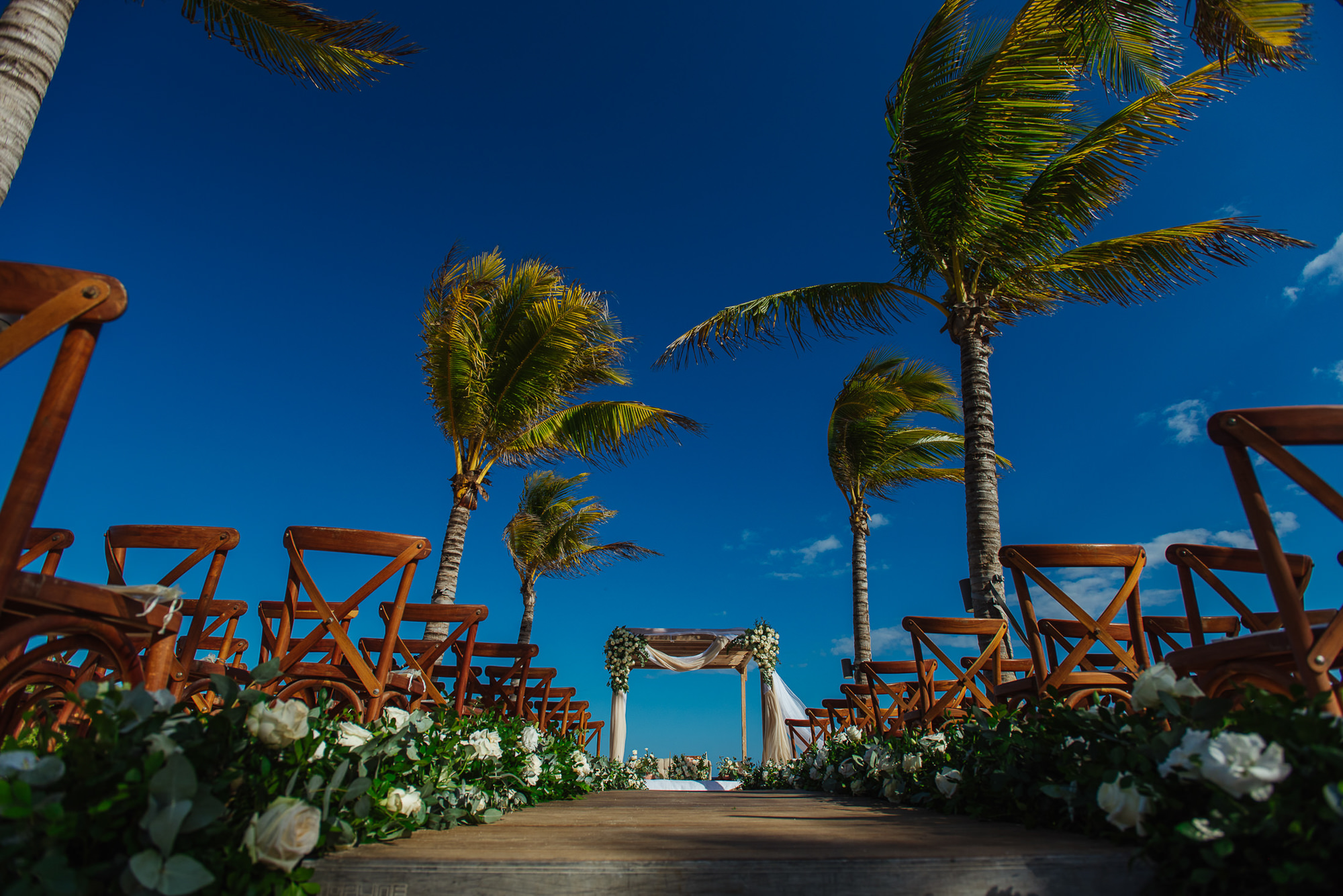 Ceremony aisle decor against palm trees and blue sky, by Citlalli Rico