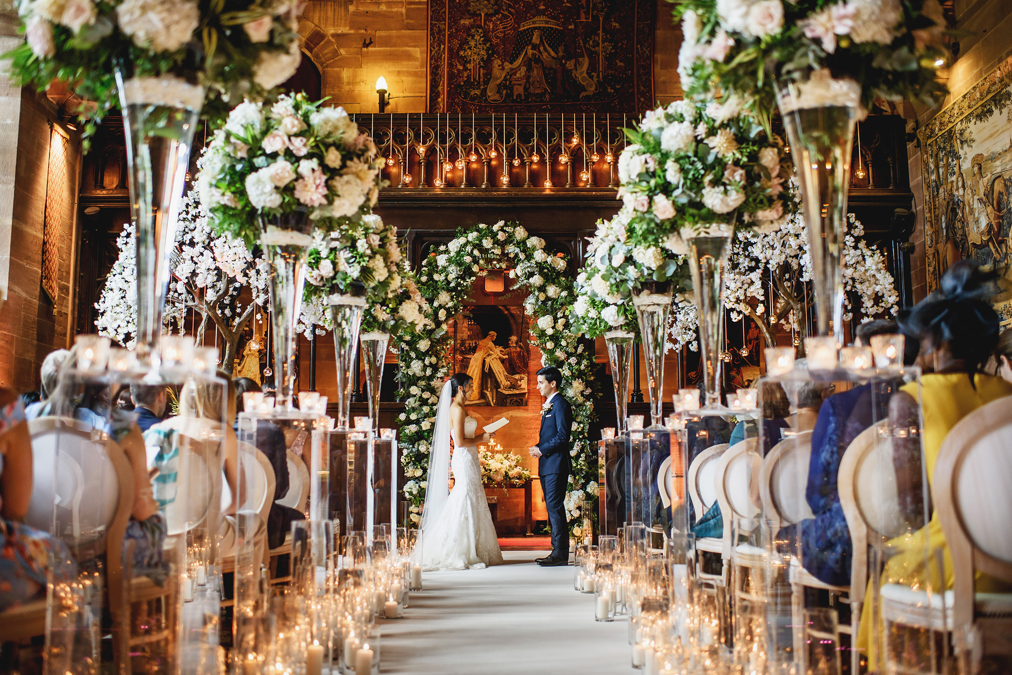 Ceremony with tall glass flower vases - photo by Ross Harvey