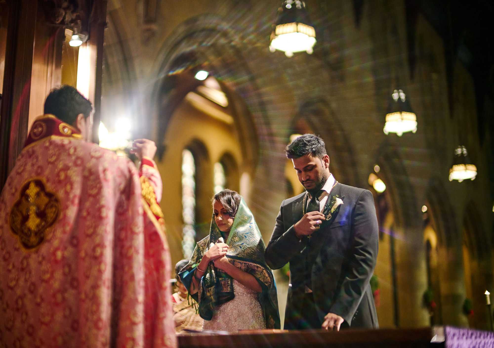 Bride and groom being blessed at Catholic church wedding ceremony, photo by The Brenizers