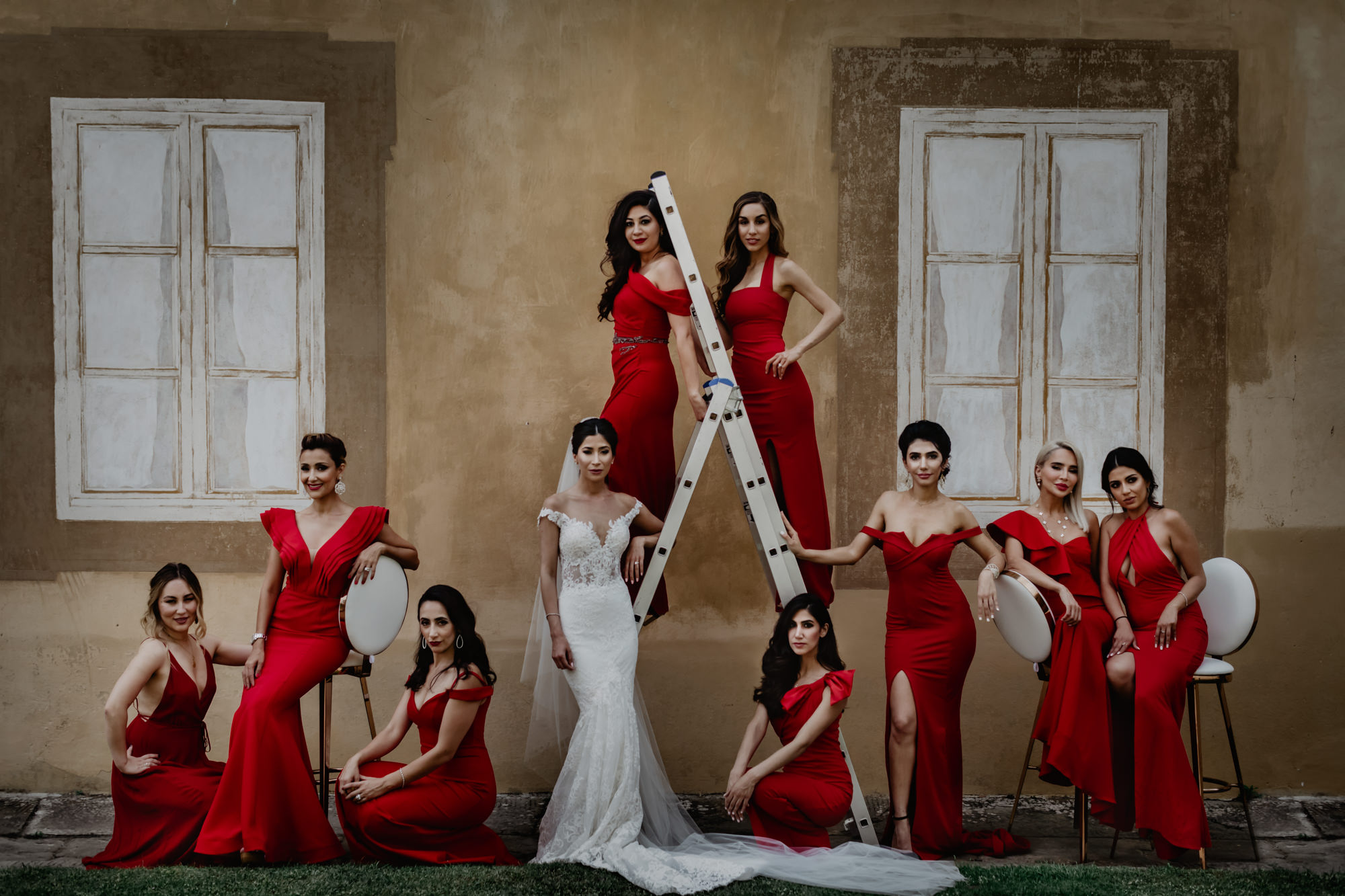 Elegant bridal party in red silk dresses with bride - portrait by David Bastianoni