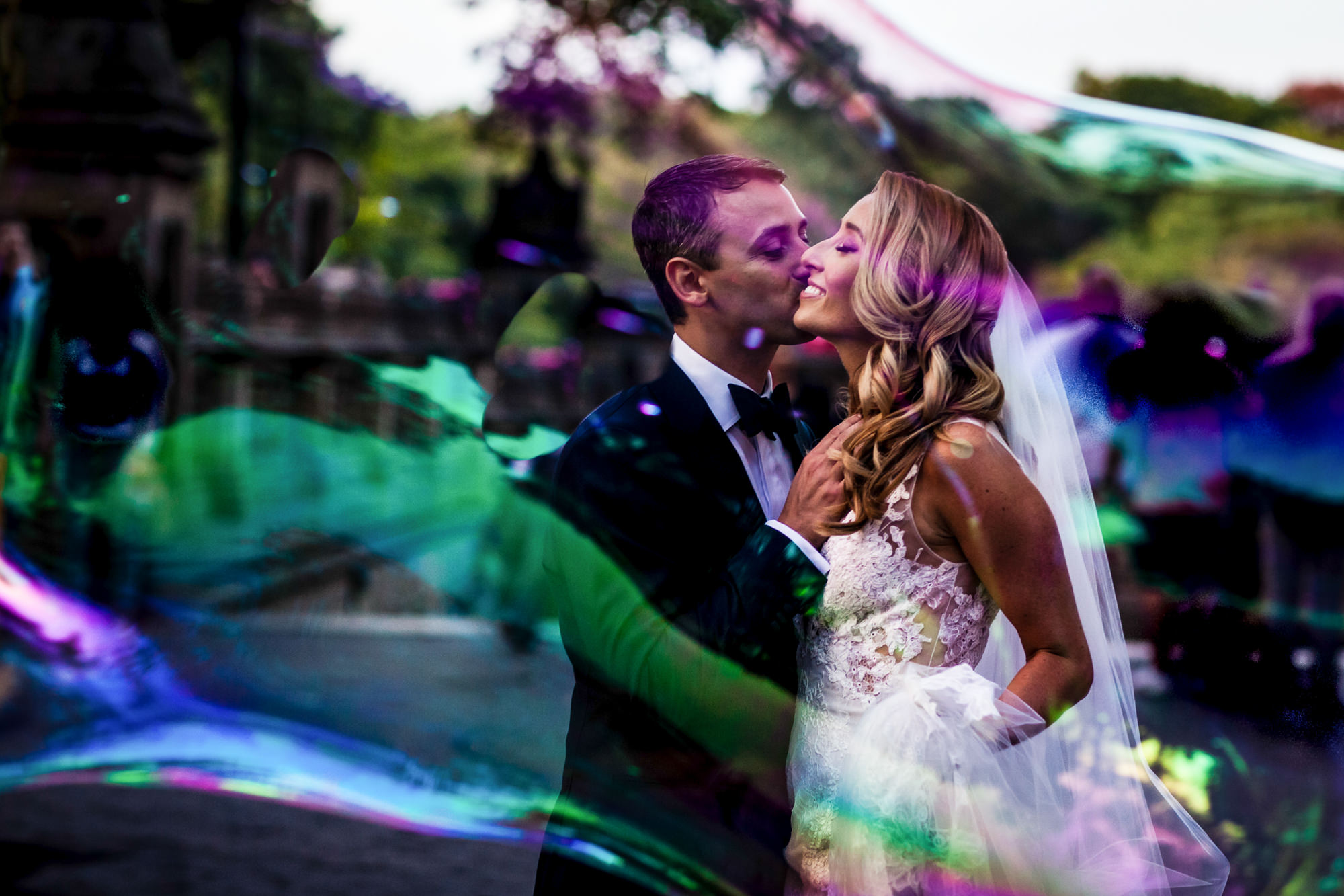 Colorful bride and groom portrait through huge soap bubble - photo by JAG Studios