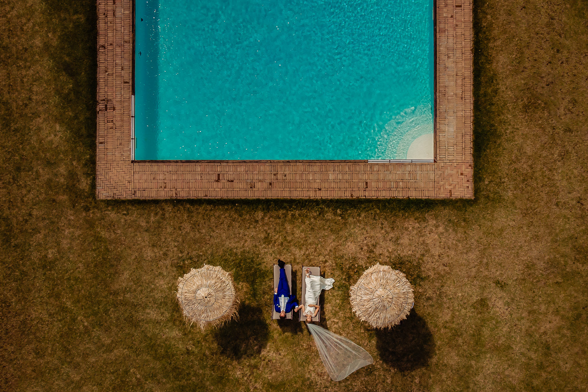 Drone shot of couple laying on lounge chairs by pool, by Eppel Fotographie