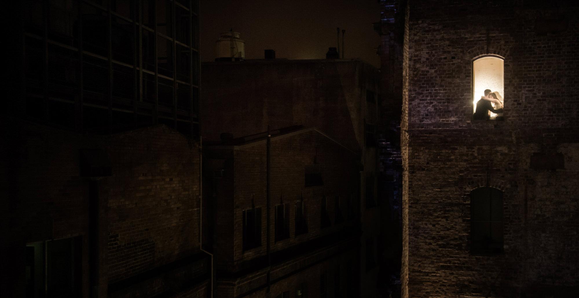 Moody portrait of couple in window of brick building - Studio Impressions