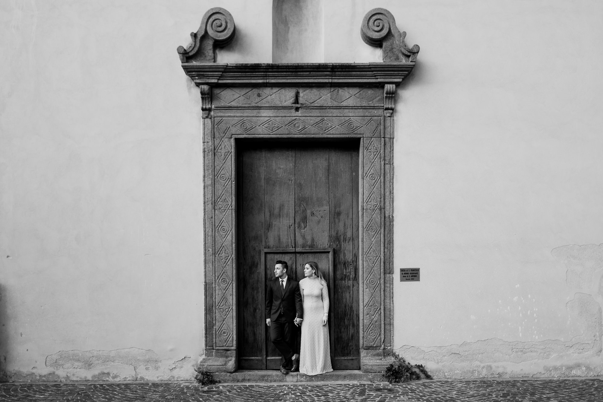 Couple holding hands in front of Nordic carved door photo by Nordica Photography