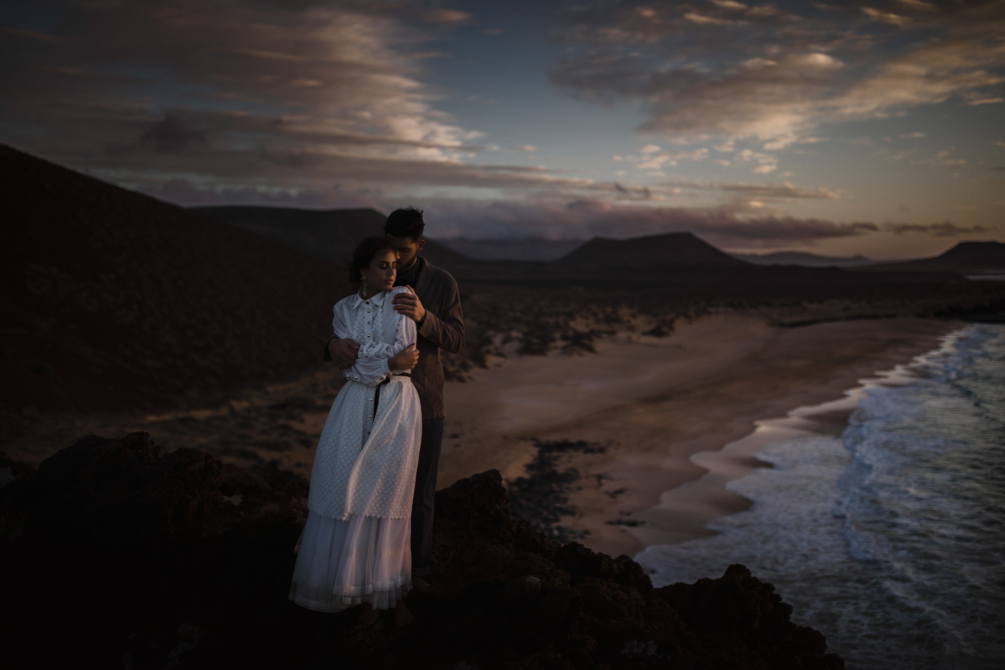 Couple above beach bride in modest cotton gown - McClintock Photography Agency