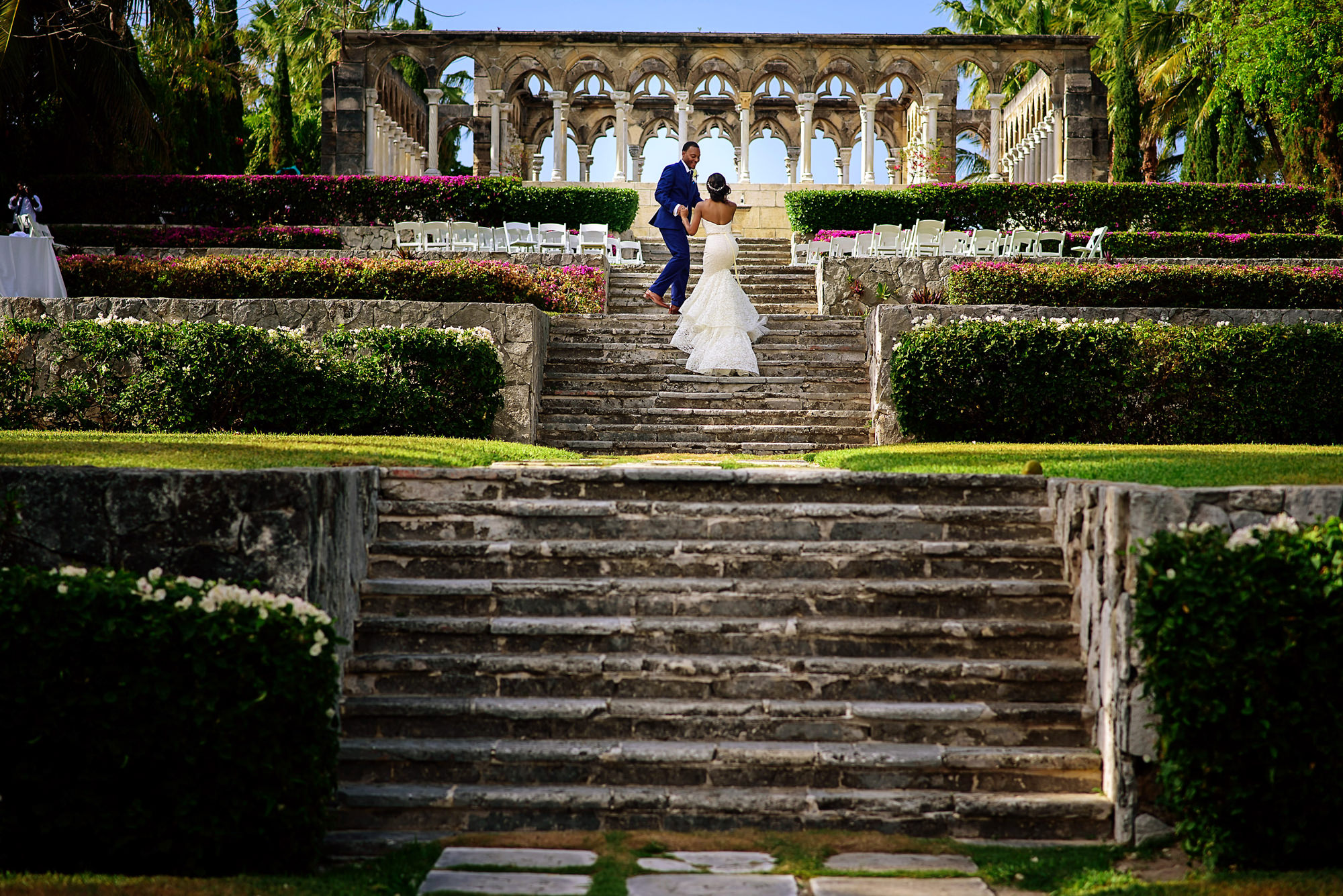 Couple walk to ceremony area up roman garden stairs - photo by Jide Alakija