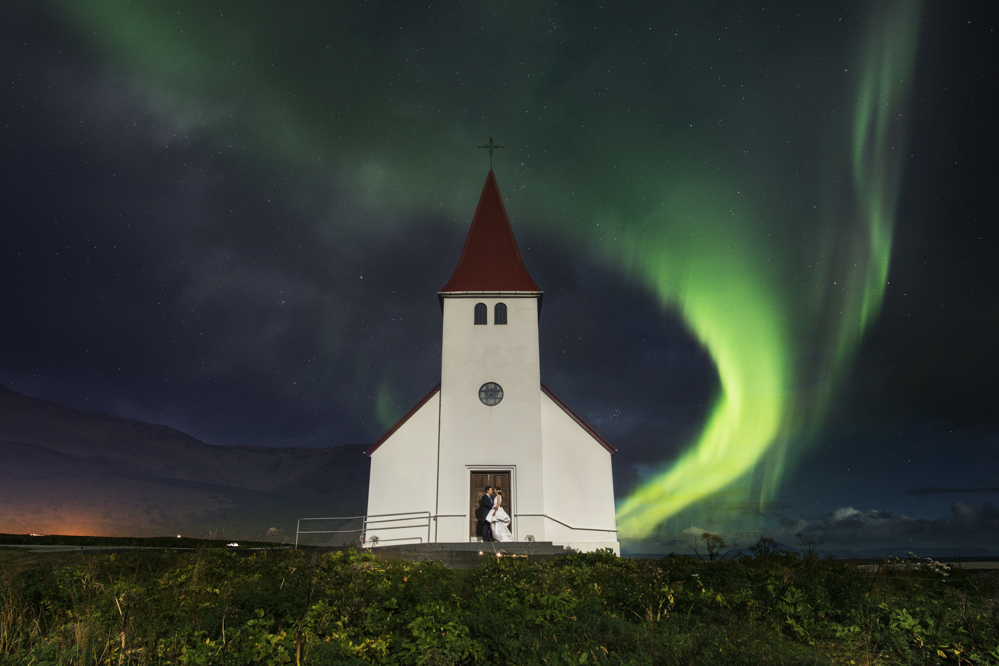 Couple at chapel with northern lights - photo by Look Fotographica