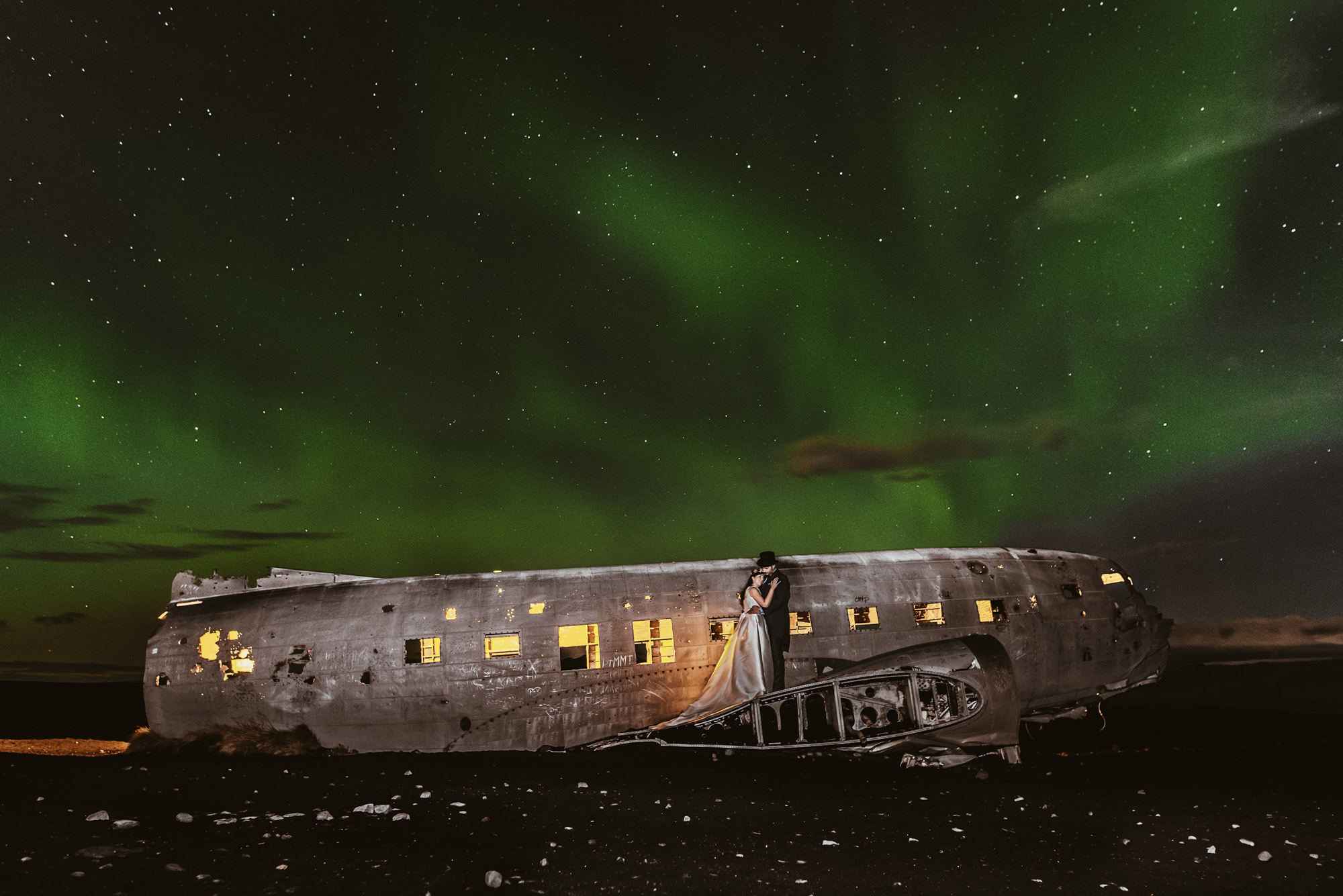 Couple at plane wreck with Northern Lights - photo by Look Fotographia