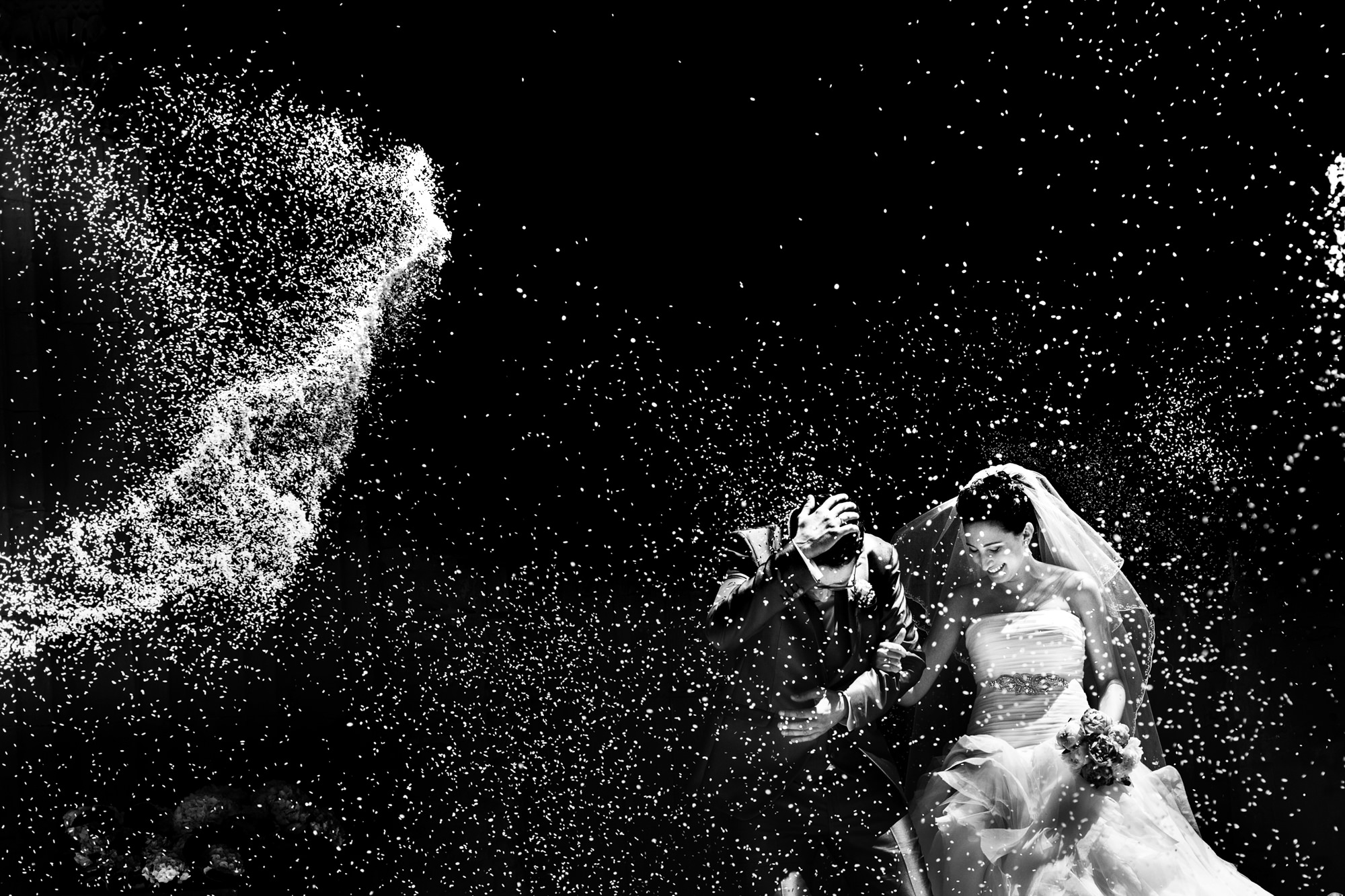 Couple being showered with rice - black and white - photo by Look Fotographica