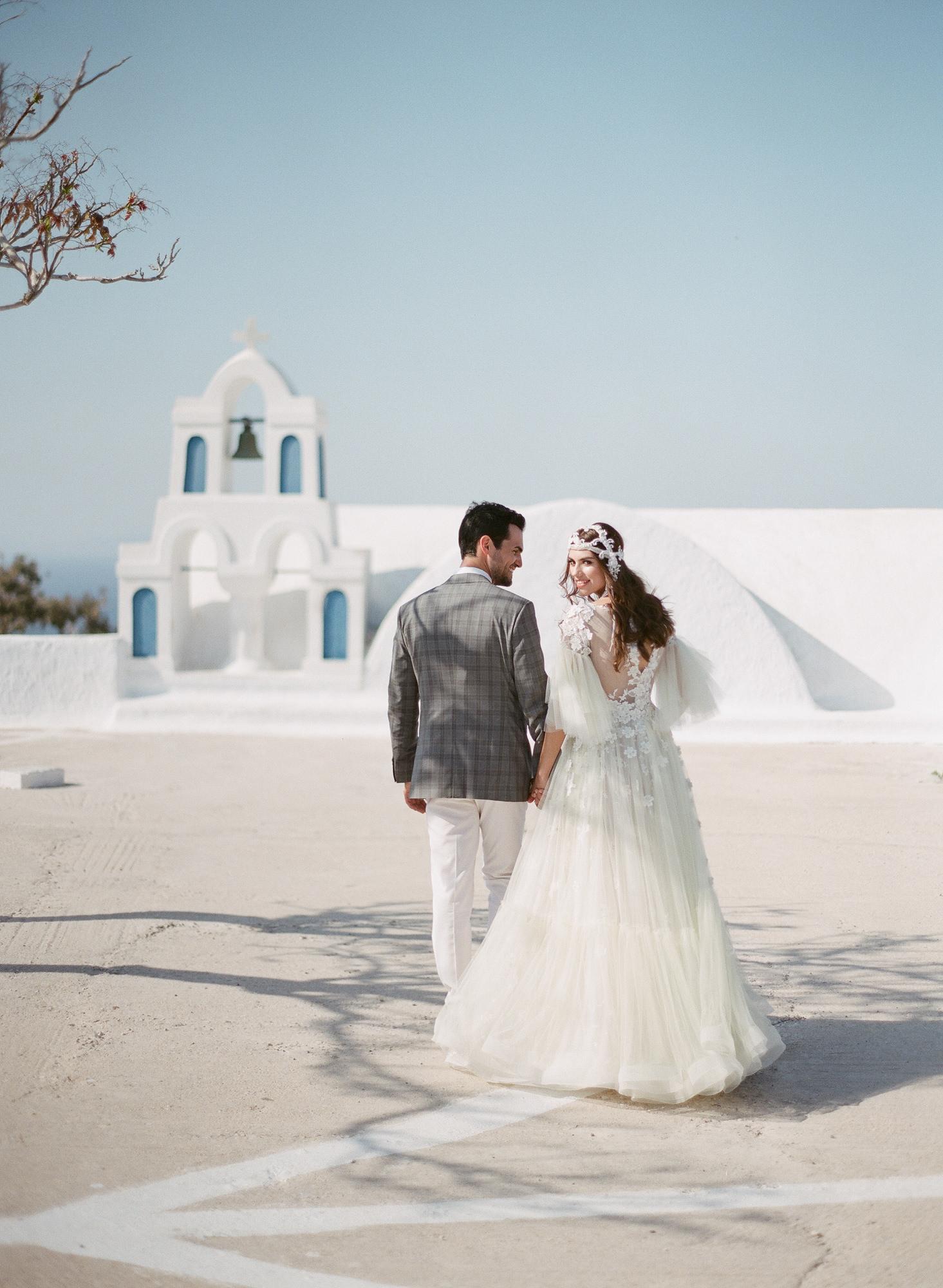 Couple walking to white stucco church - photo by Gianluca Adoviaso Photography