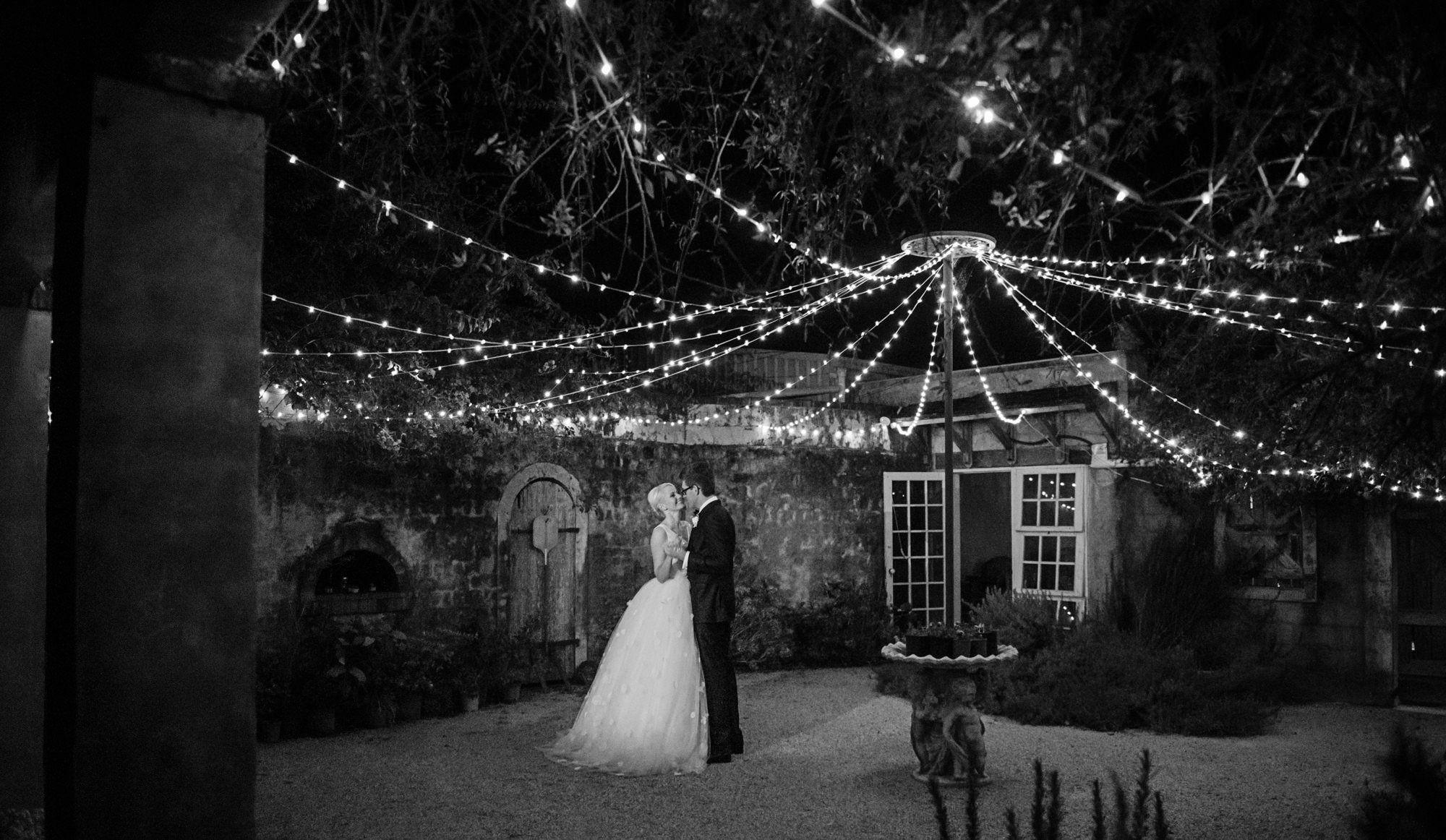 Couple dancing alone under string lights - Studio Impressions Photography