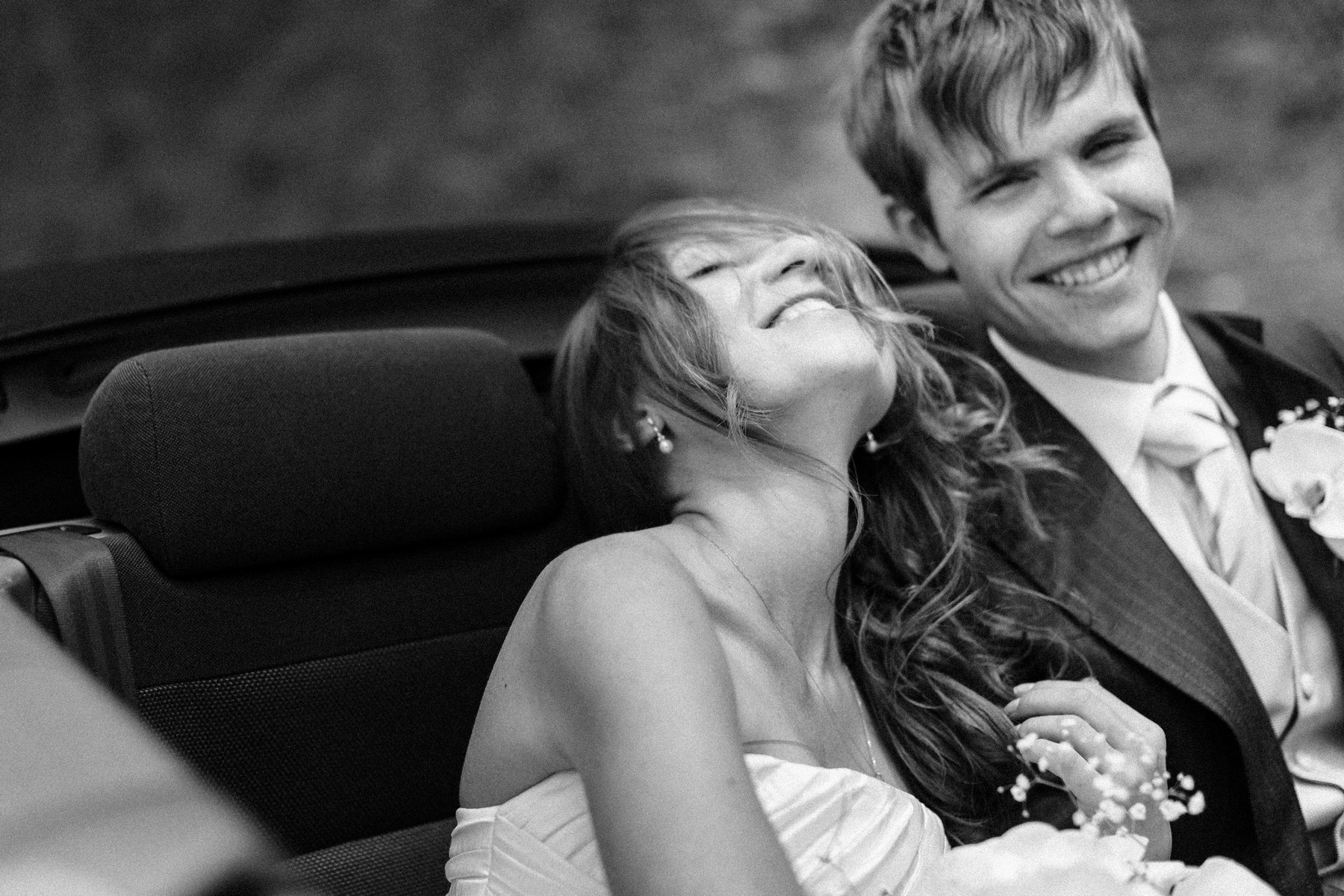 Blissful portrait of couple driving away from ceremony - John and Joseph Photography