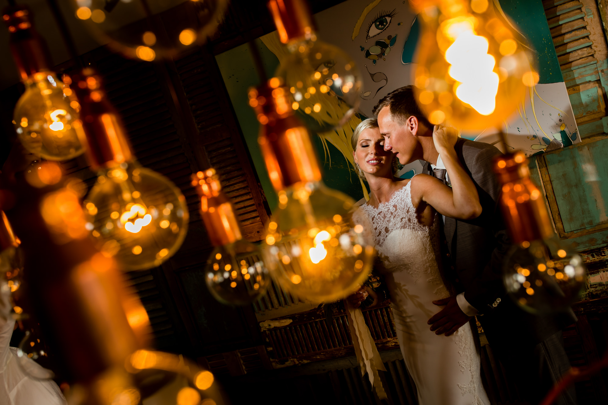 Bride and groom portrait framed by tungsten light bulbs, by Eppel Fotographie