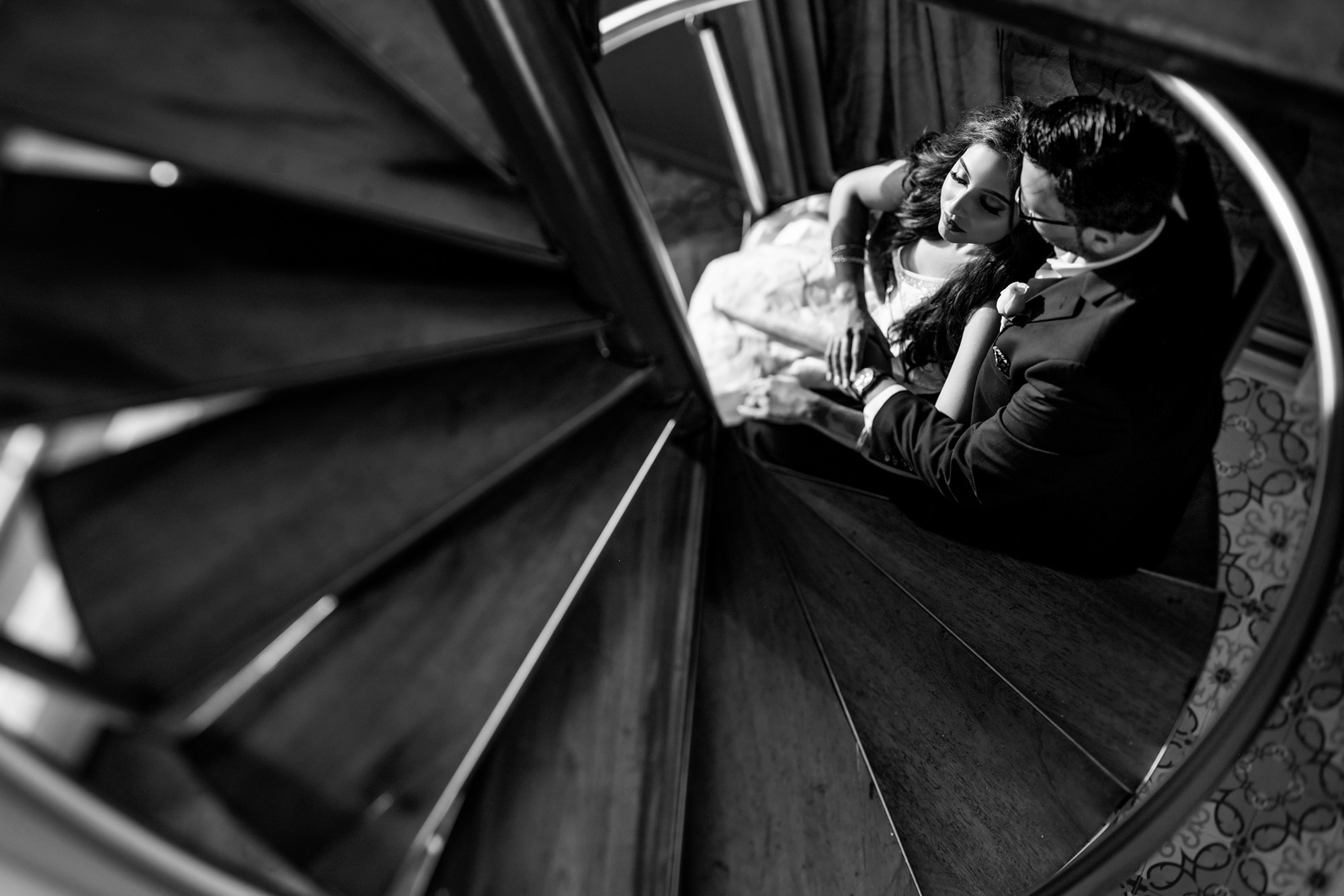 Couple embraces  at bottom of circular stairway - Morgan Lynn Photography
