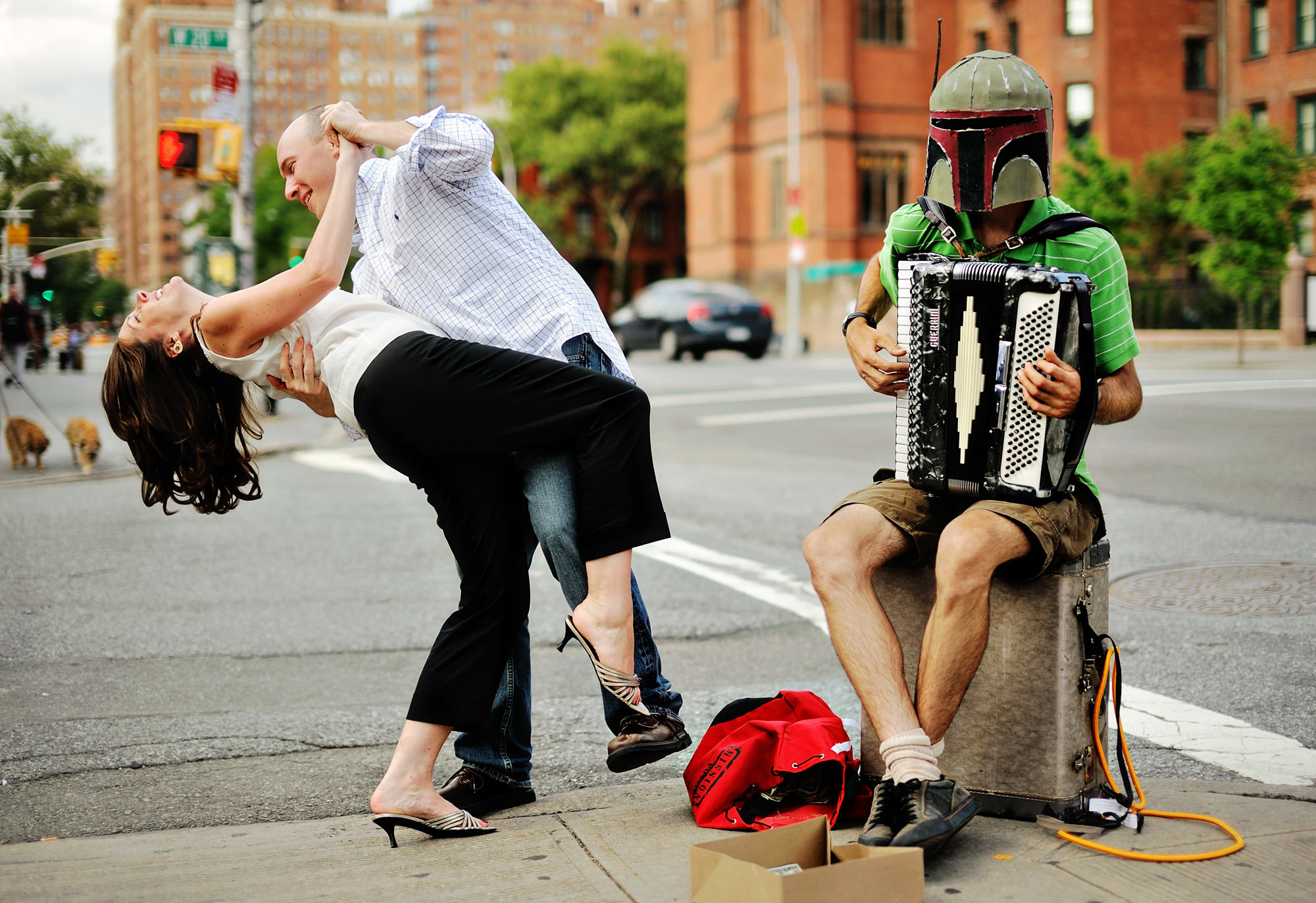 Fun engagement portrait of couple dipping next to accordion busker, photo by The Brenizers