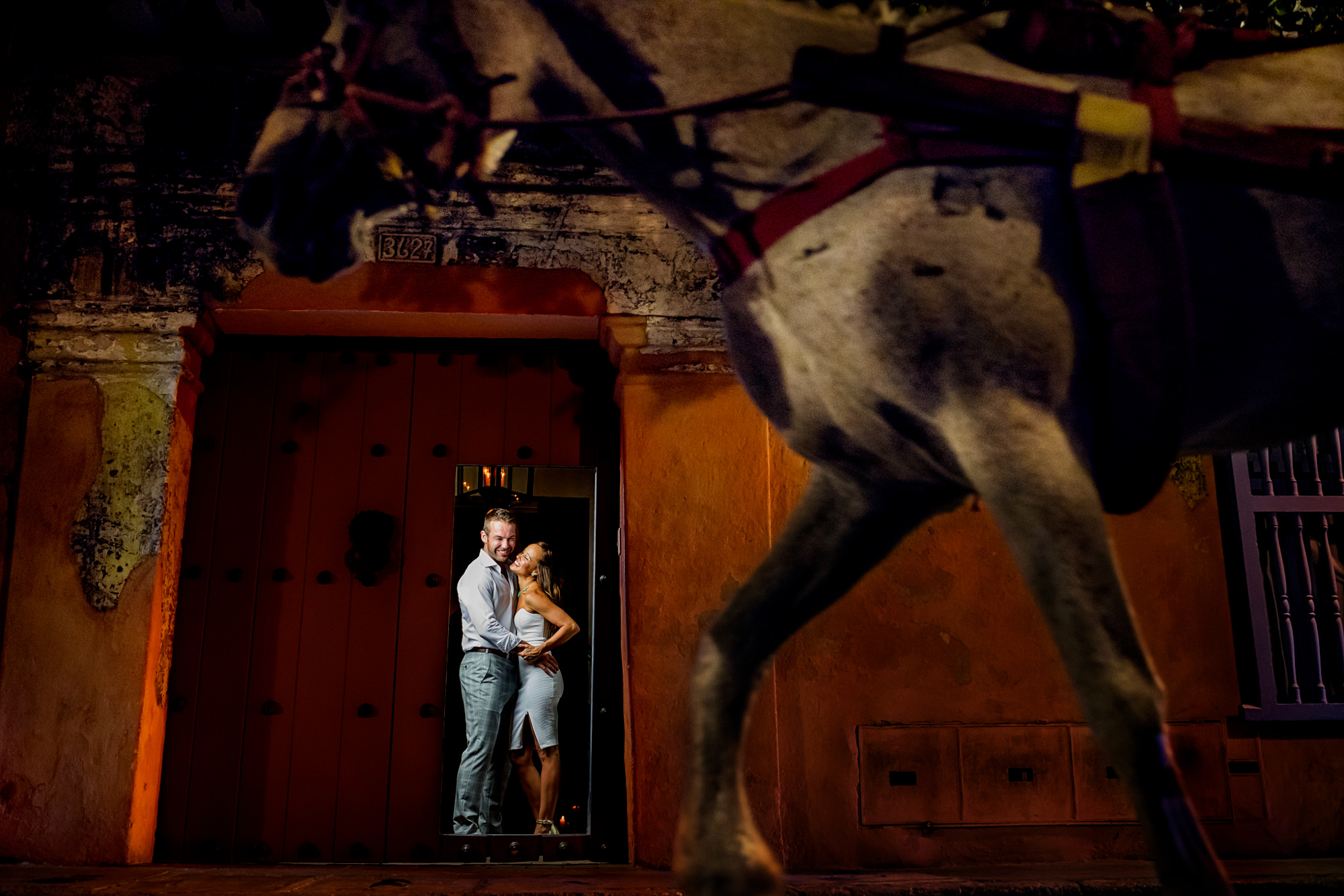 Horse passing by couple in stucco doorway