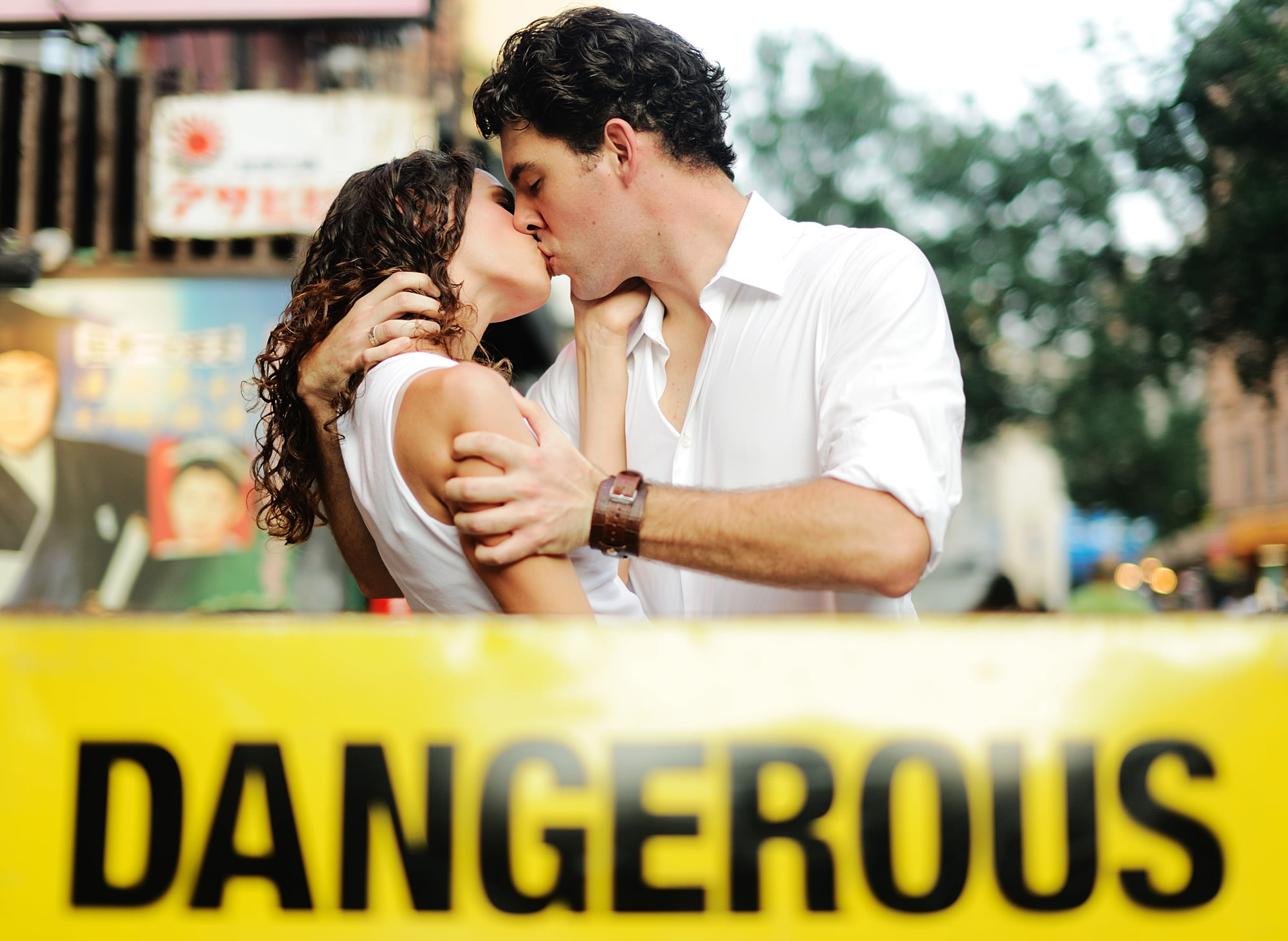 Creative engagement portrait couple kissing in front of Dangerous yellow tape, by The Brenizers