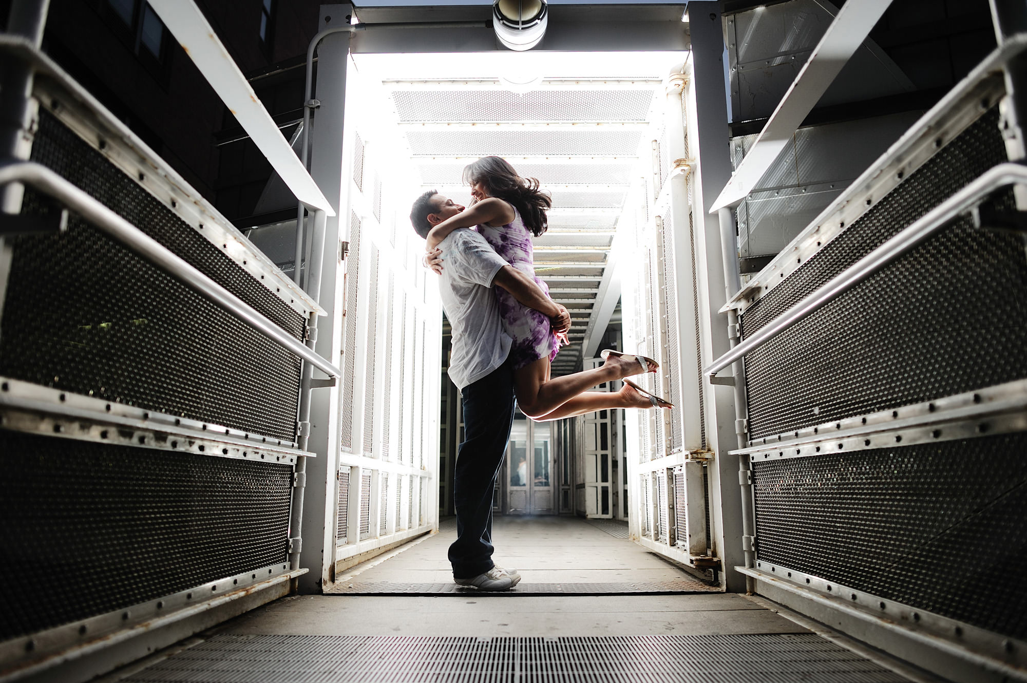 Happy engagement portrait of couple in lit corridor, photo by The Brenizers