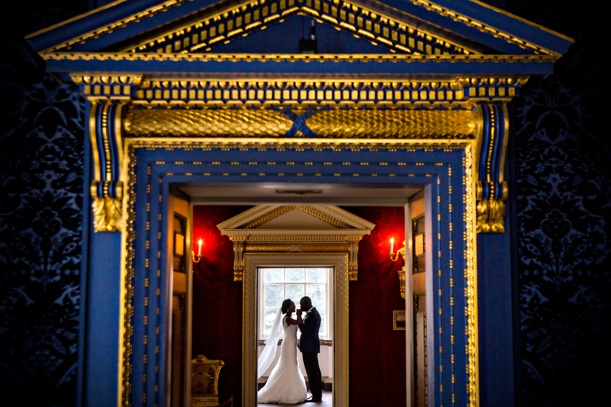 Couple under ornate gold doorway - photo by Jide Alakija