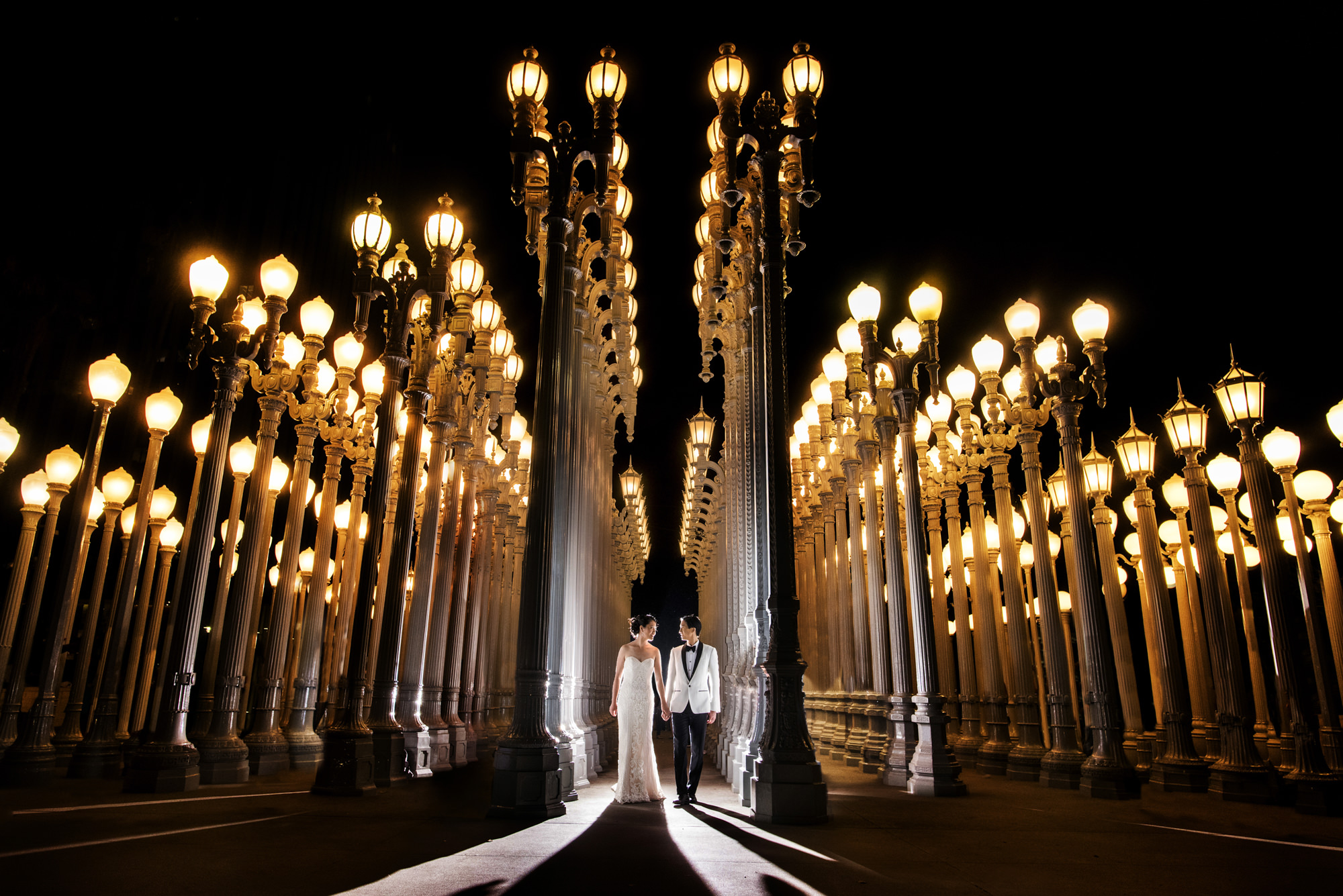 Couple in columns of gaslight lanterns - photo by Look Fotographica