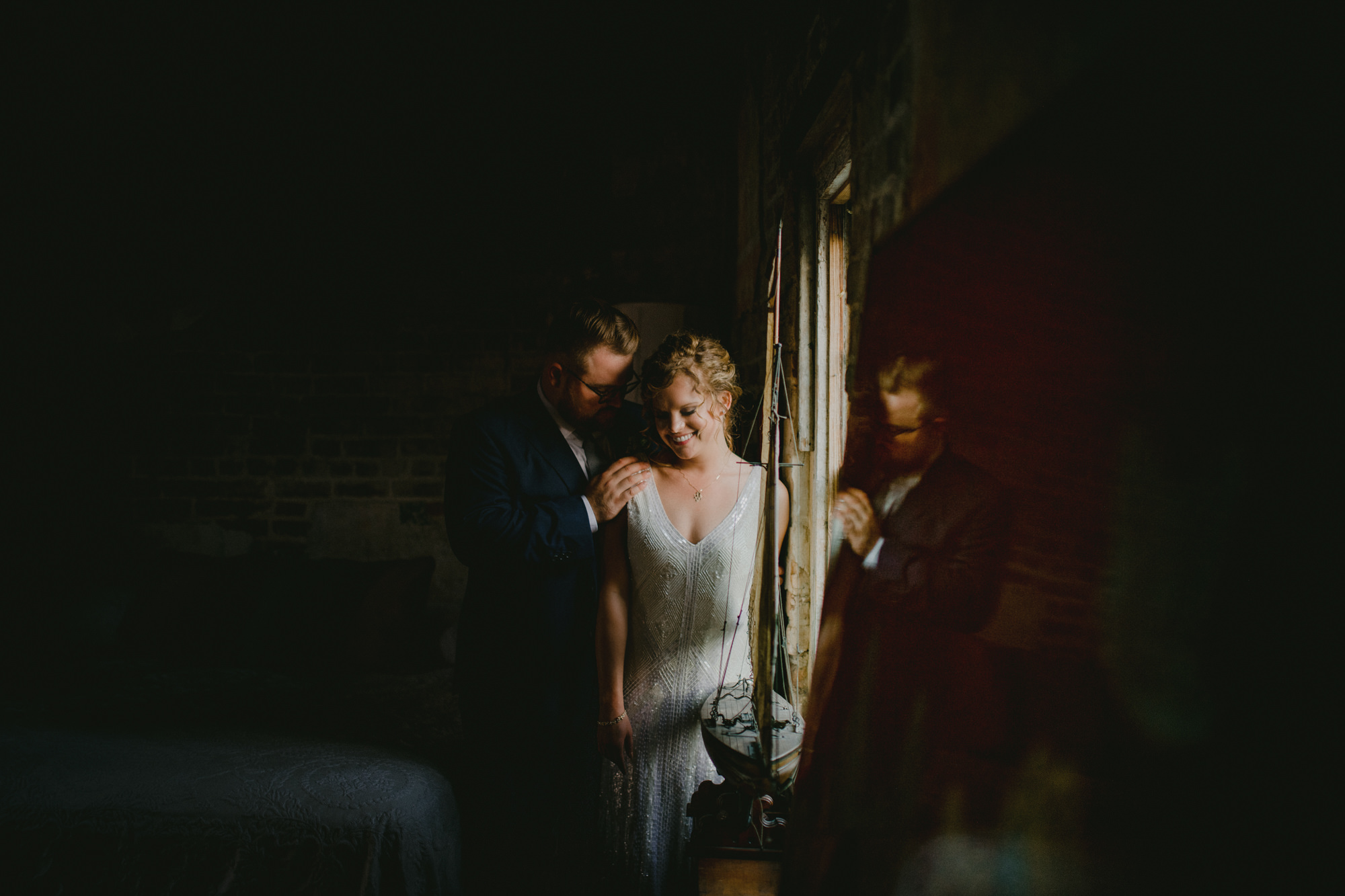 Couple in window light bride in vintage beaded dress - photo by McClintock Photography Agency
