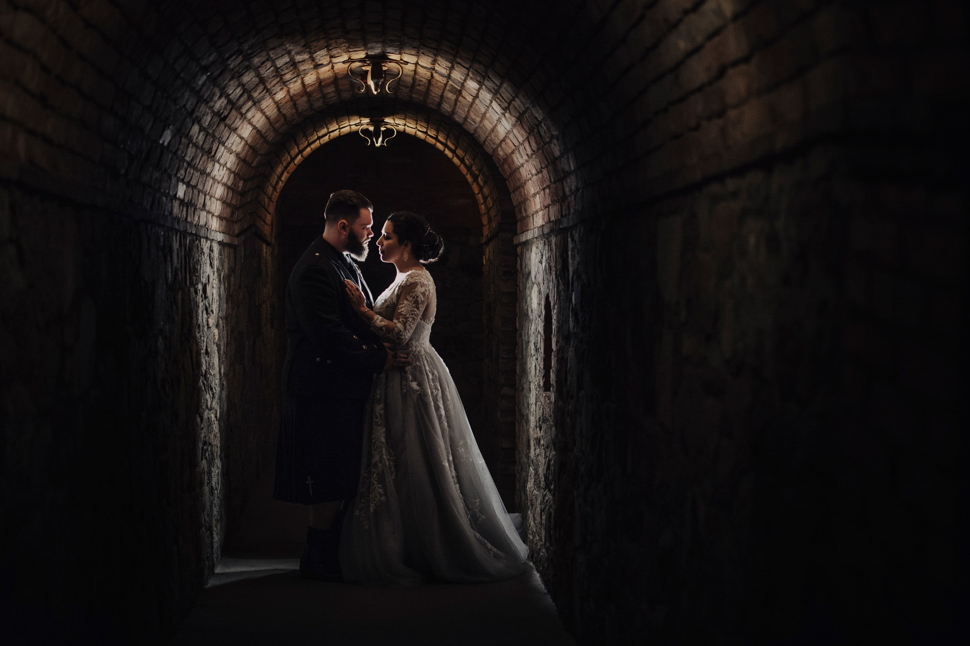 Couple in window-lit archway - photo by Jerry Ghionis