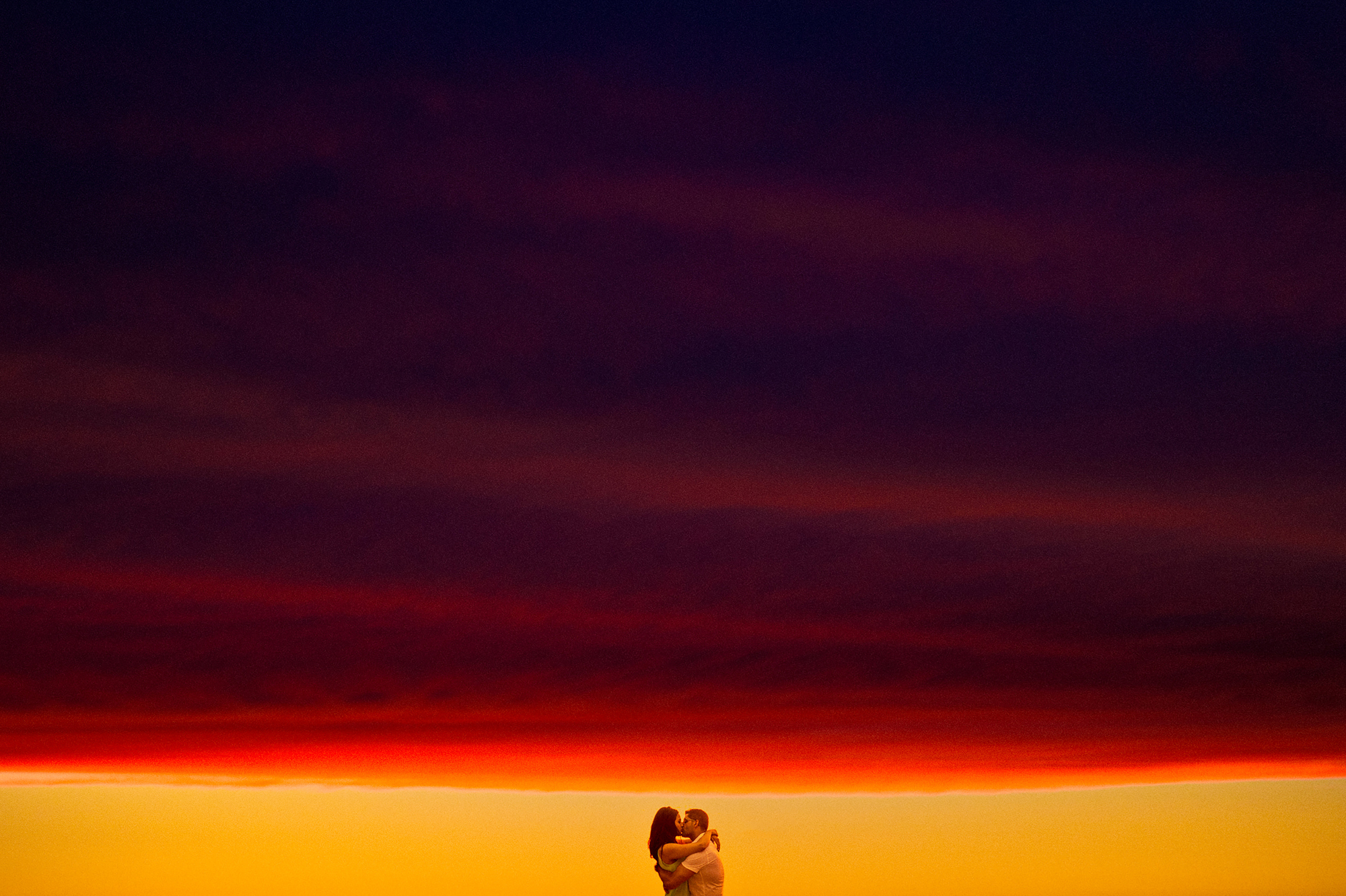Couple kisses under electric red sunset - photo by Cooked Photography