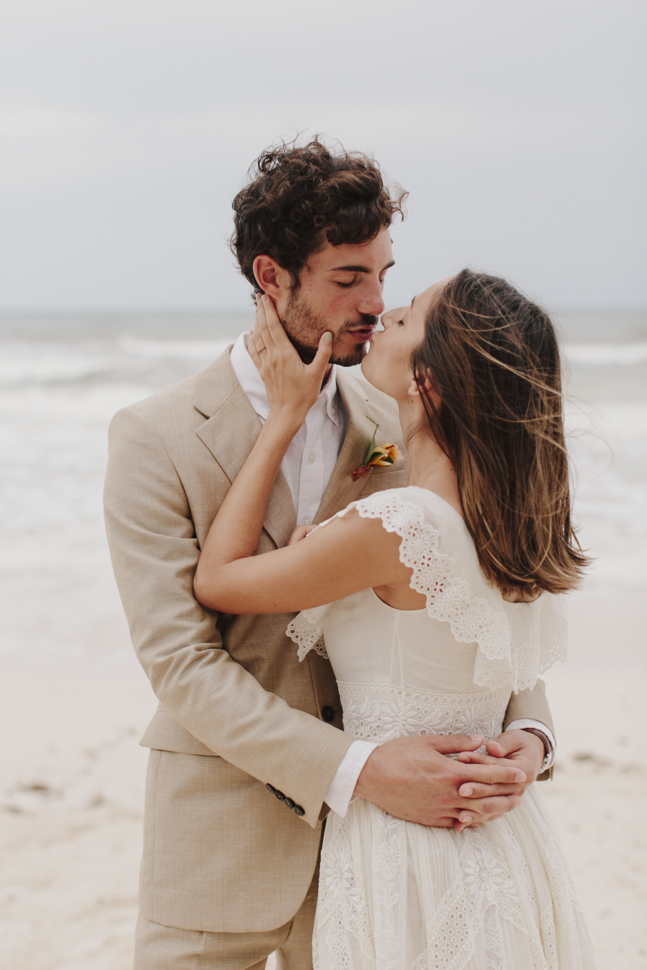 Romantic photo of couple kissing on beach by James Moes