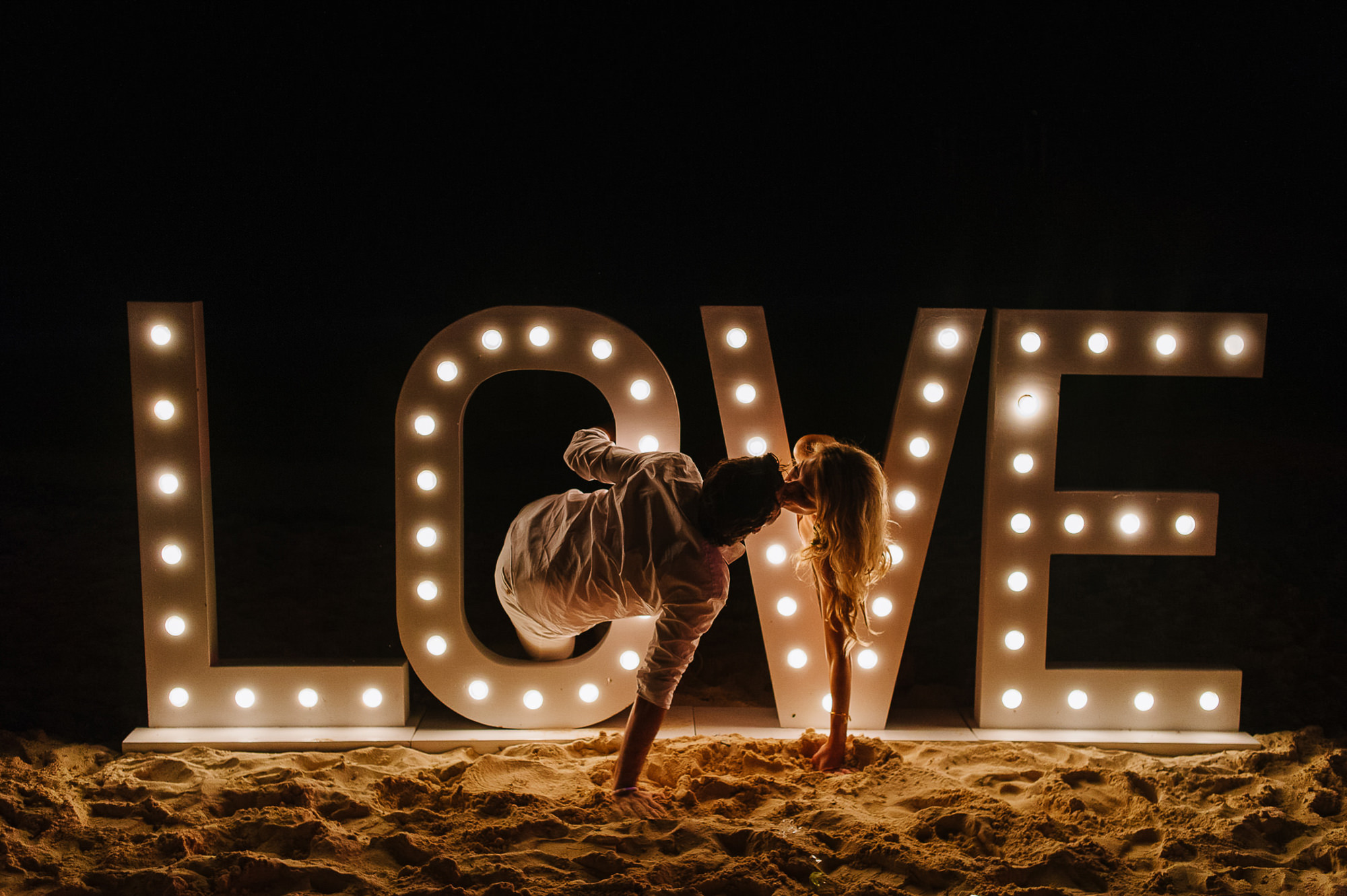 Bride and groom kiss through LOVE lit sign, by Citlalli Rico