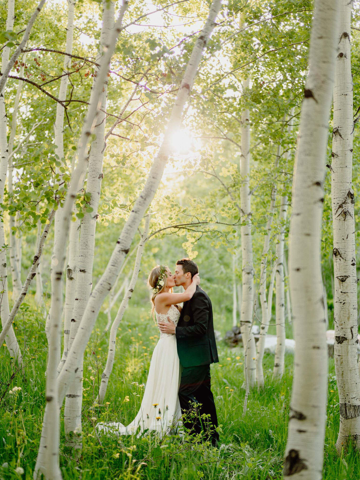 Bride in floral crown and groom kiss in birch forest, photo by Benj Haisch