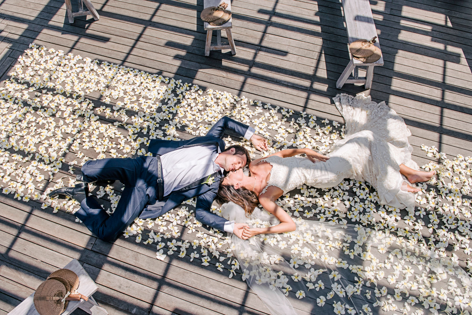Couple laying on white plumeria applique aisle runner -  Studio Impressions Photography